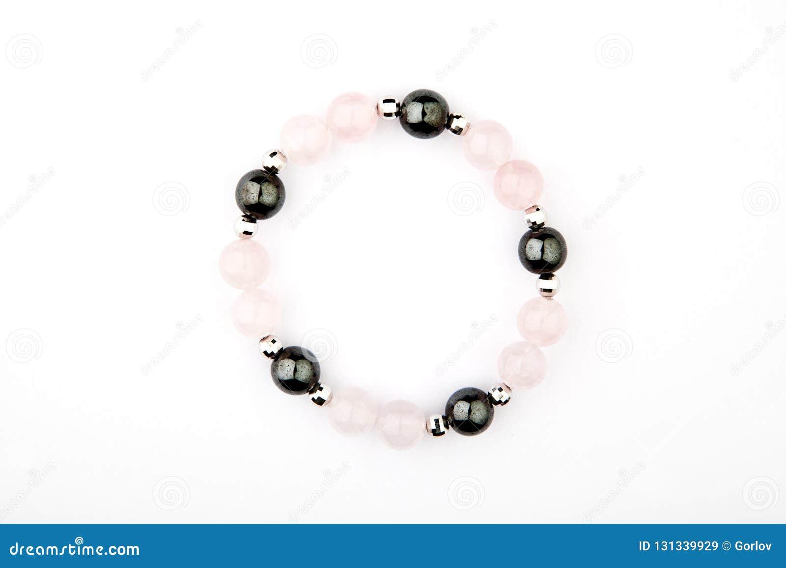 Fondo blanco de la pulsera del rosa del cuarzo de la piedra de plata del hematites