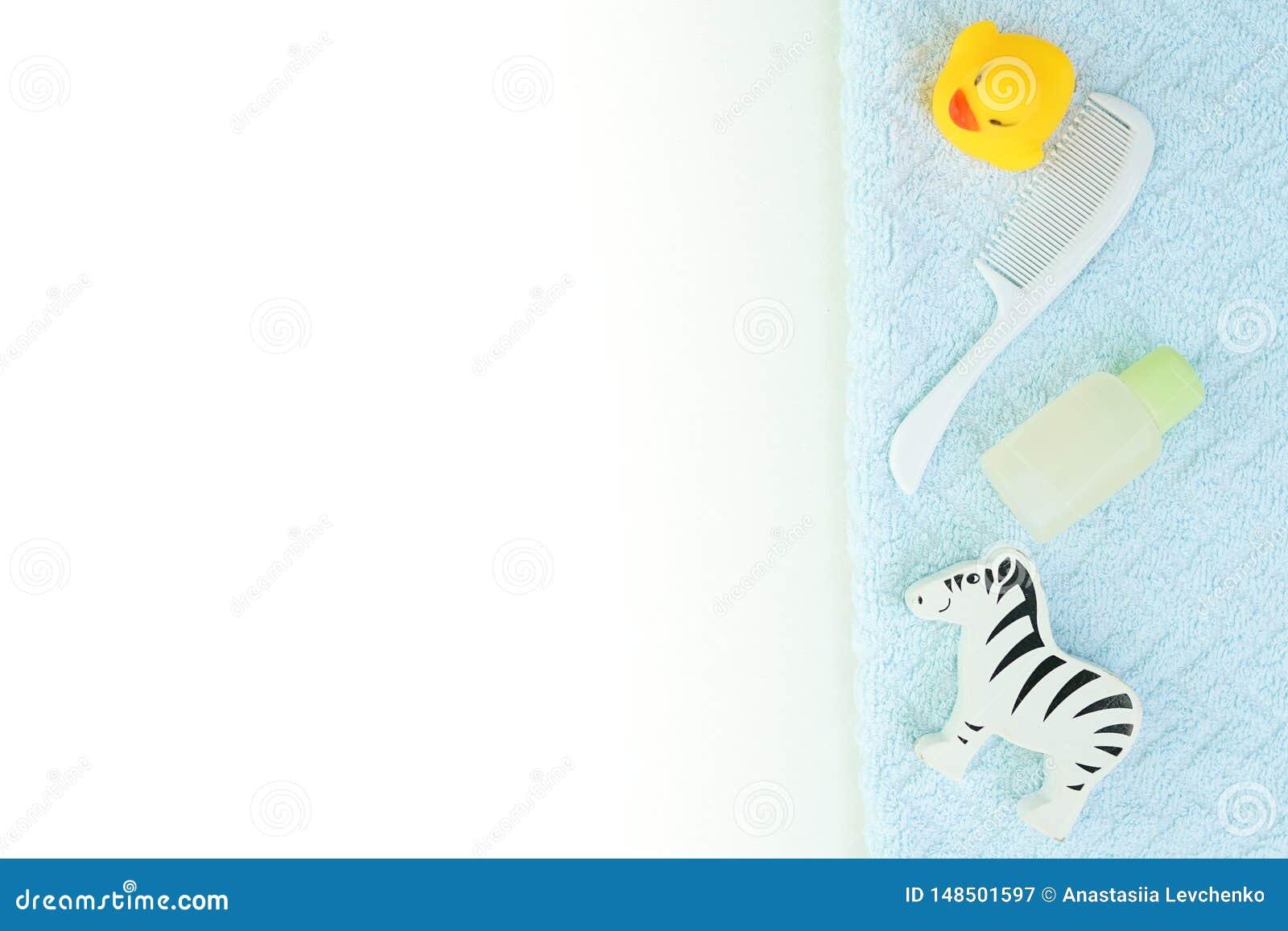 Fondo blanco puesto plano del baño del bebé con el espacio de la copia botella del champú, cepillo para el pelo, aceite esencial,