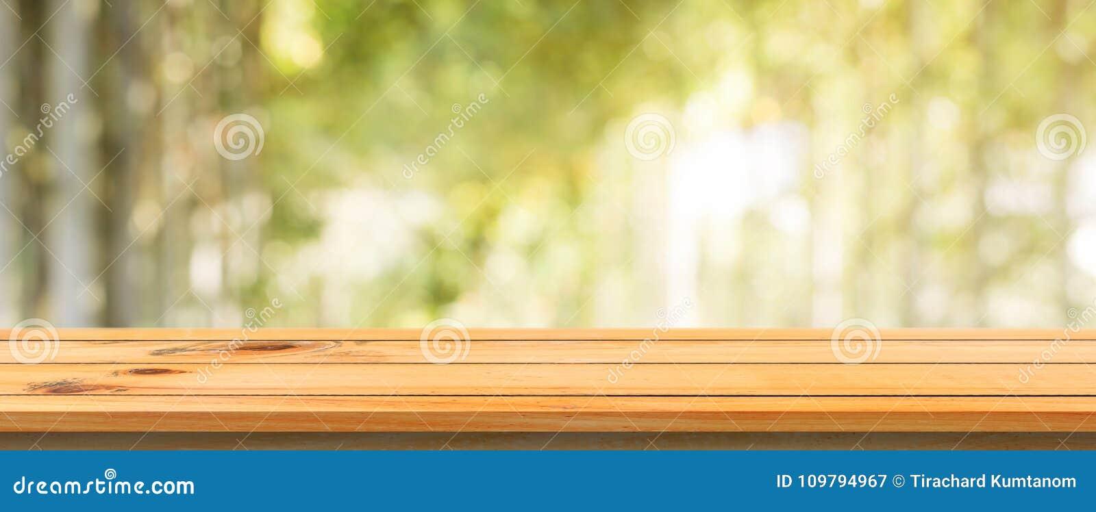 Fondo borroso tabla vacía del tablero de madera Tabla de madera marrón de la perspectiva sobre fondo del bosque de los árboles de
