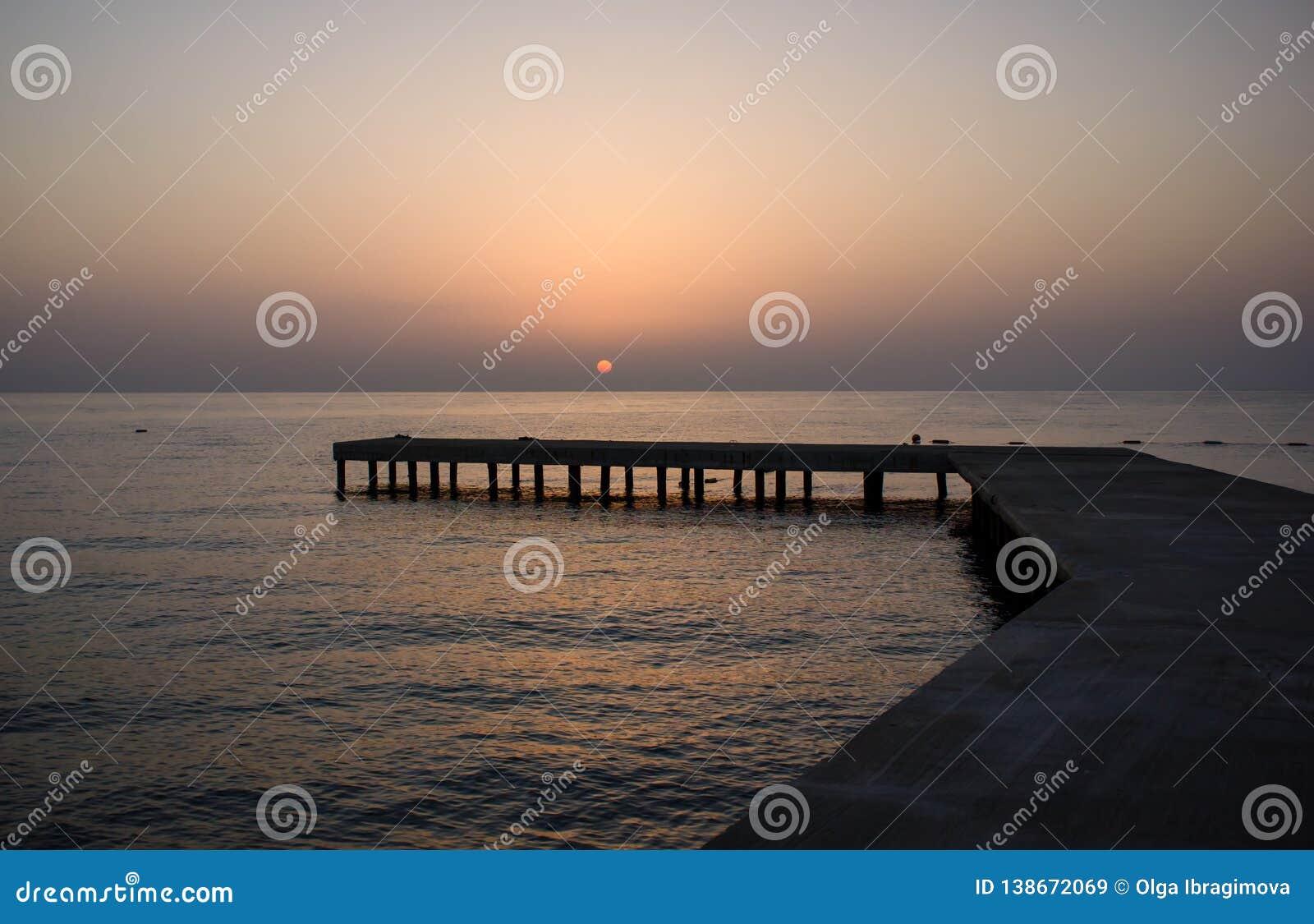 Fondo con el embarcadero de madera viejo en el mar en la puesta del sol