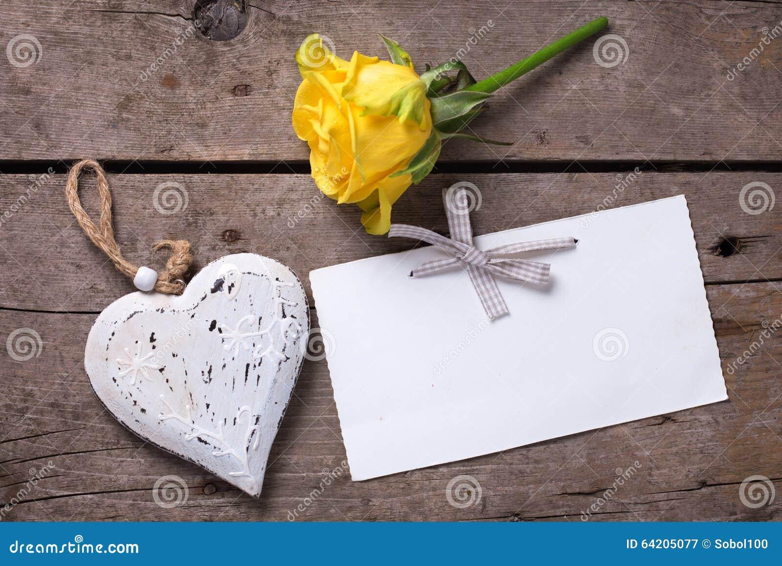 Fondo con la rosa hermosa del amarillo, el corazón decorativo y t