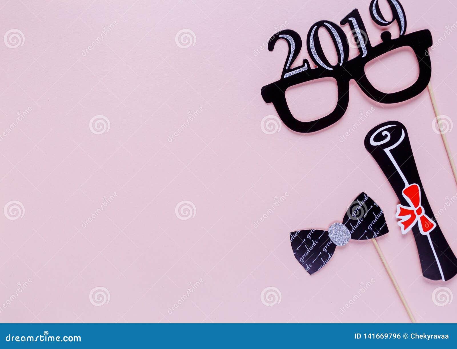 Fondo creativo con i puntelli del photobooth per la graduazione: cappelli, diploma, vetri, labbra su fondo di carta rosa pastello
