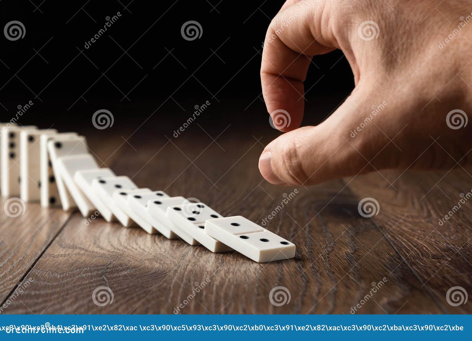 Fondo creativo, domin?s blancos que empujan manualmente masculinos, en un fondo de madera marr?n Concepto de efecto de domin?, ca