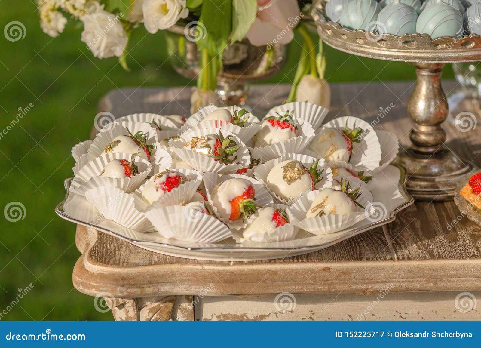 Fondo dai dessert assortiti per gli ospiti di una festa nuziale o di una fragola di compleanno in cioccolato al latte bianco