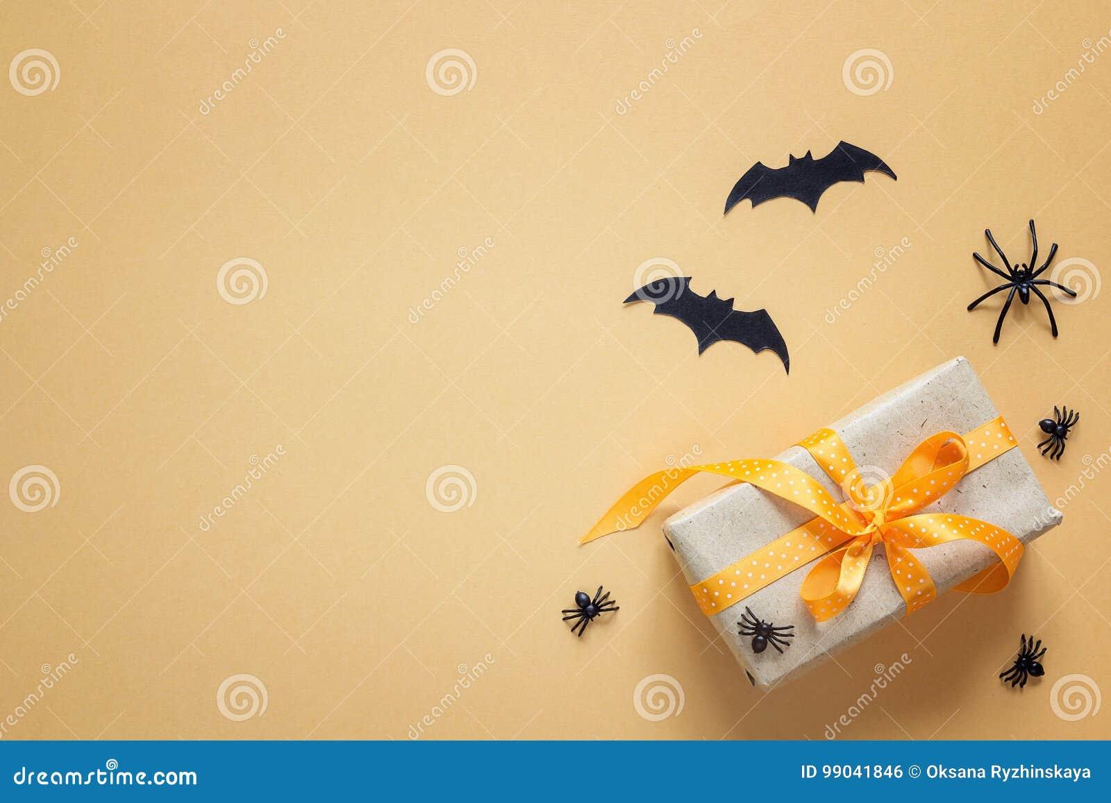 Fondo de Halloween con la caja de regalo, las arañas decorativas y los palos
