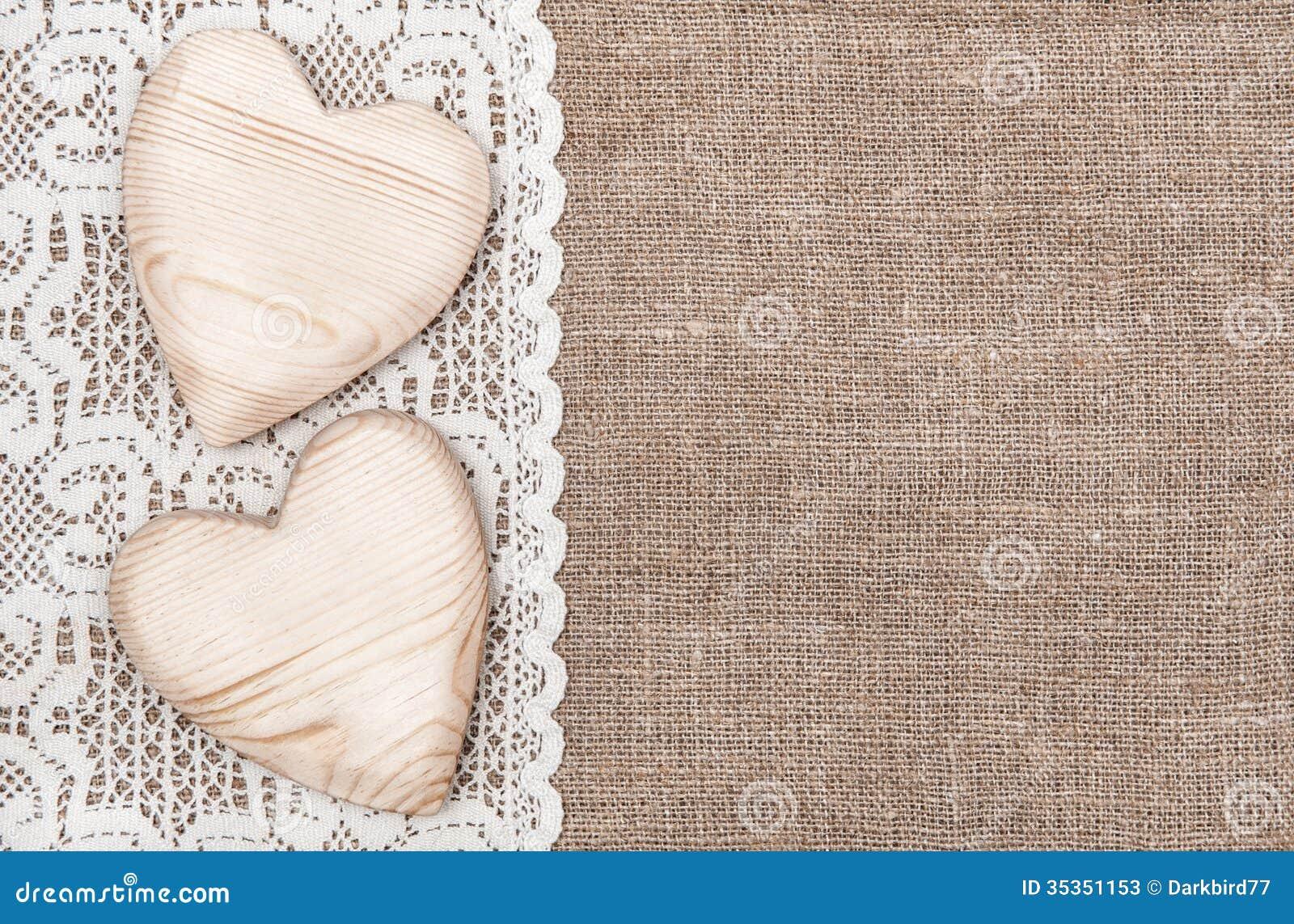 Fondo de la arpillera con el paño de encaje y los corazones de madera