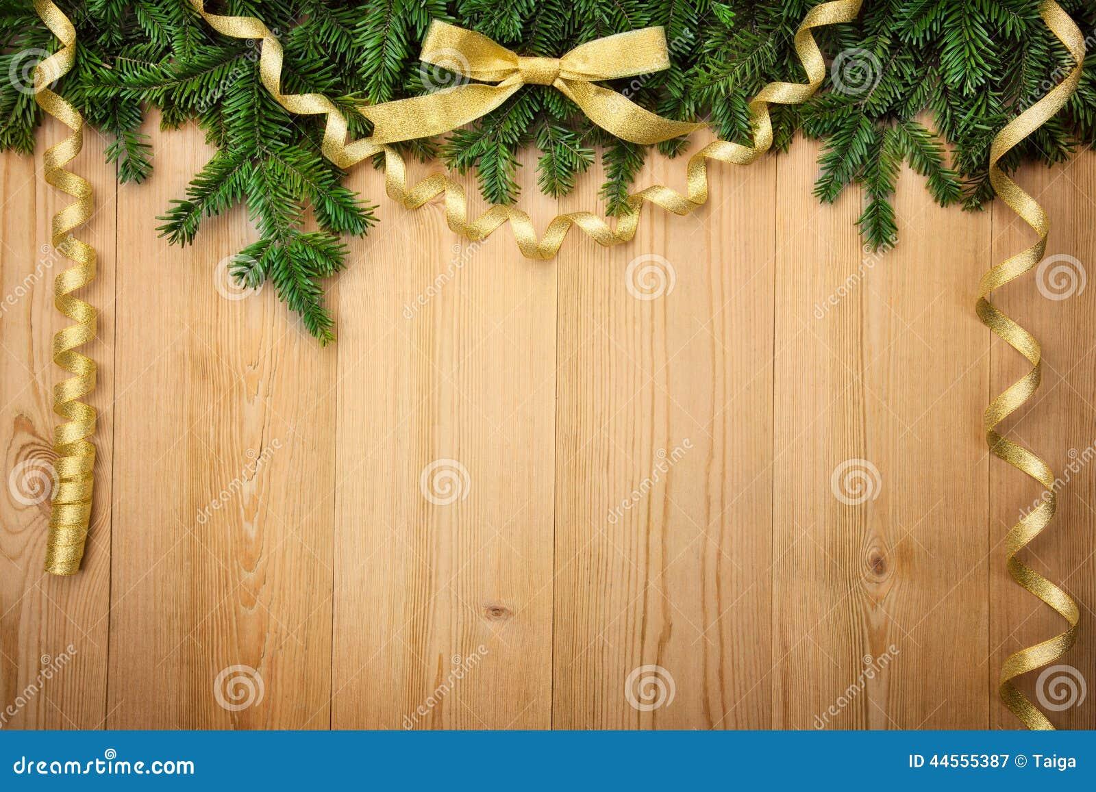 Fondo de la Navidad con el abeto, el arco y las cintas en la madera
