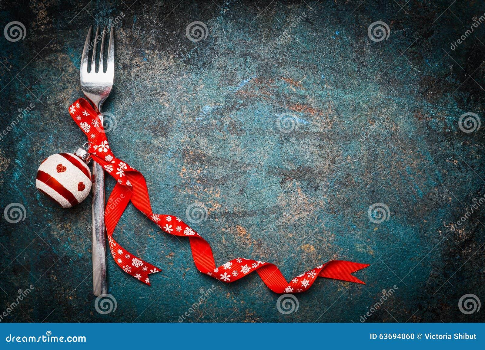 Fondo de la Navidad para la cena festiva con la bifurcación y decoración roja en fondo del vintage