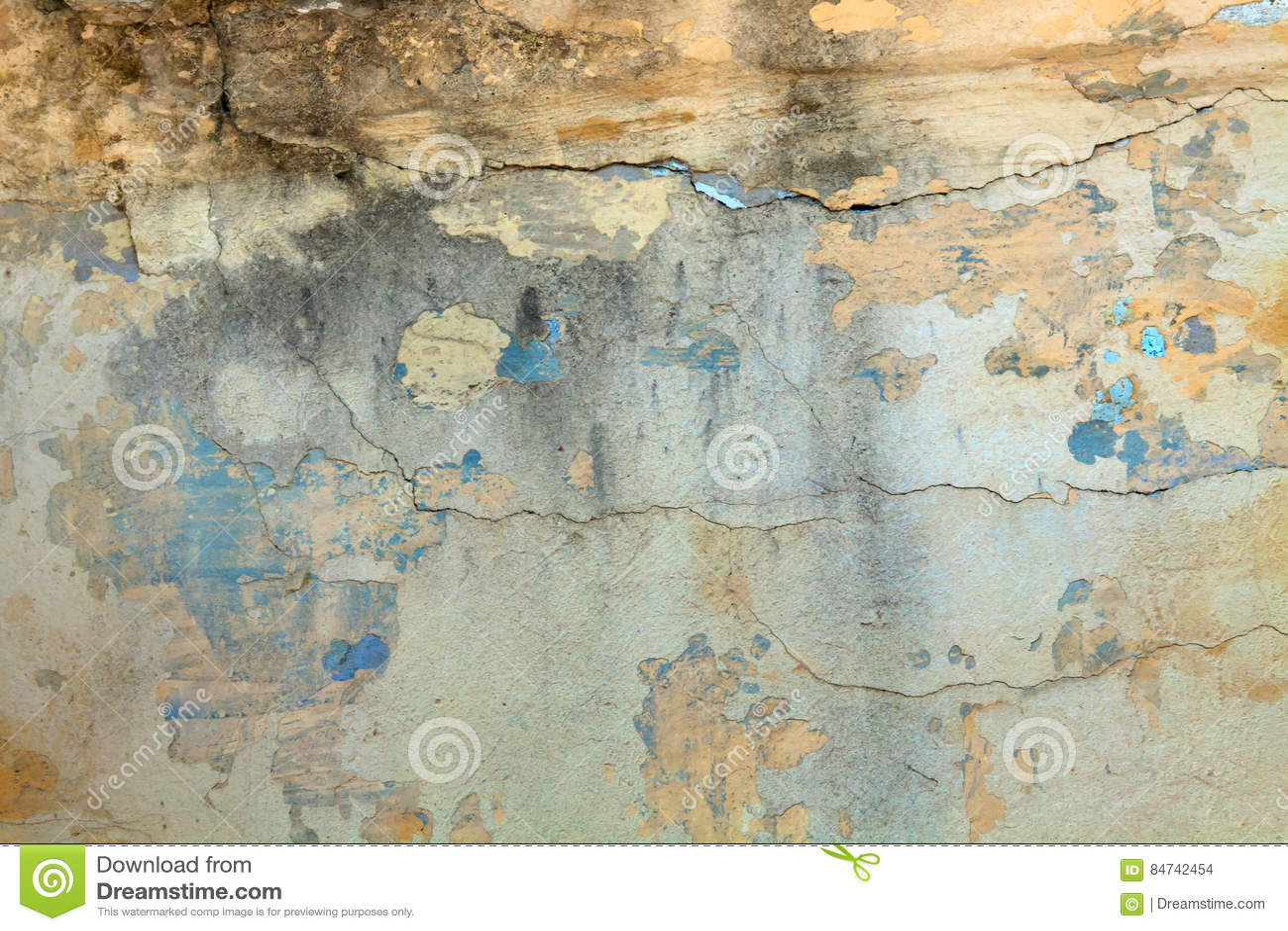 Fondo de la pared amarilla vieja con las grietas y la pintura azul