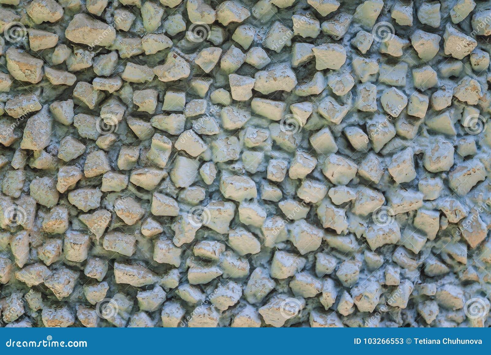 Fondo de la pared de piedra vieja con la pintura azul de la peladura