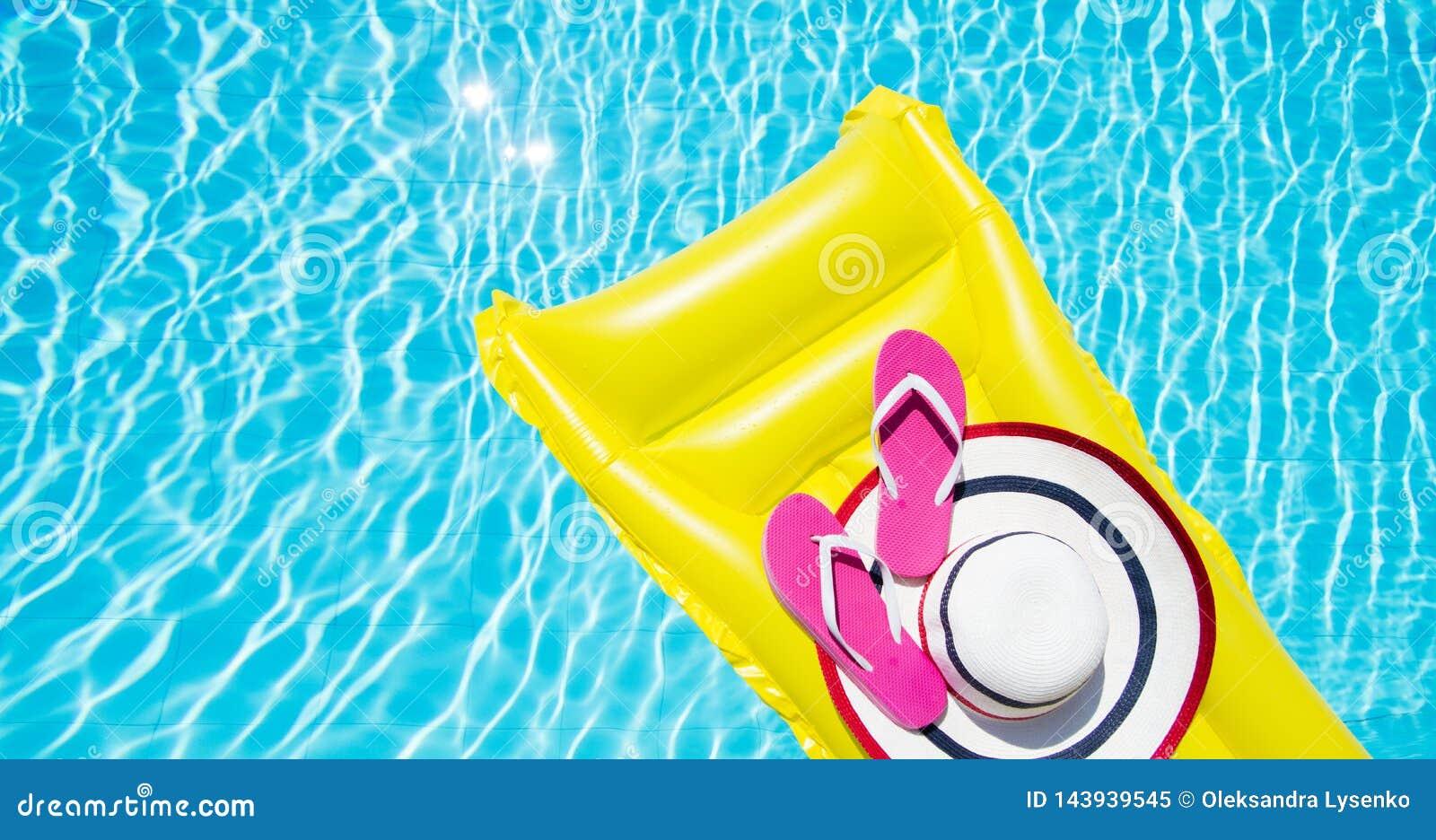 Fondo de las vacaciones de verano de la playa Colchón, chancletas y sombrero de aire inflable en piscina Lilo y verano amarillos