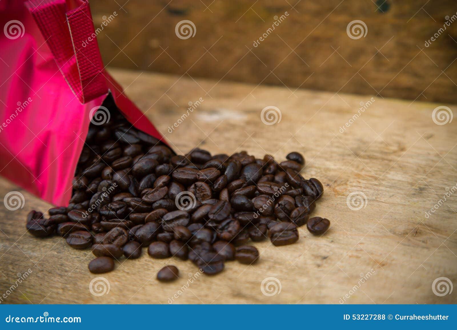 Fondo de los granos de café en los granos de café de madera, frescos con la taza de café en el fondo de madera, fondo determinado