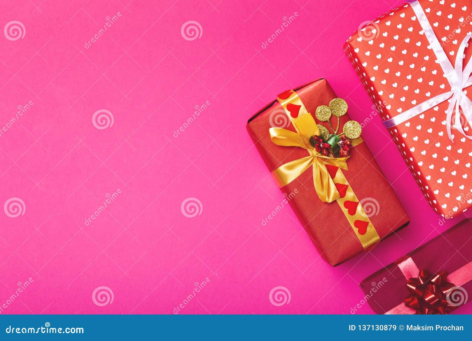 Fondo de los regalos, cajas envueltas en el documento decorativo sobre un fondo coloreado, visión superior, concepto del día de f
