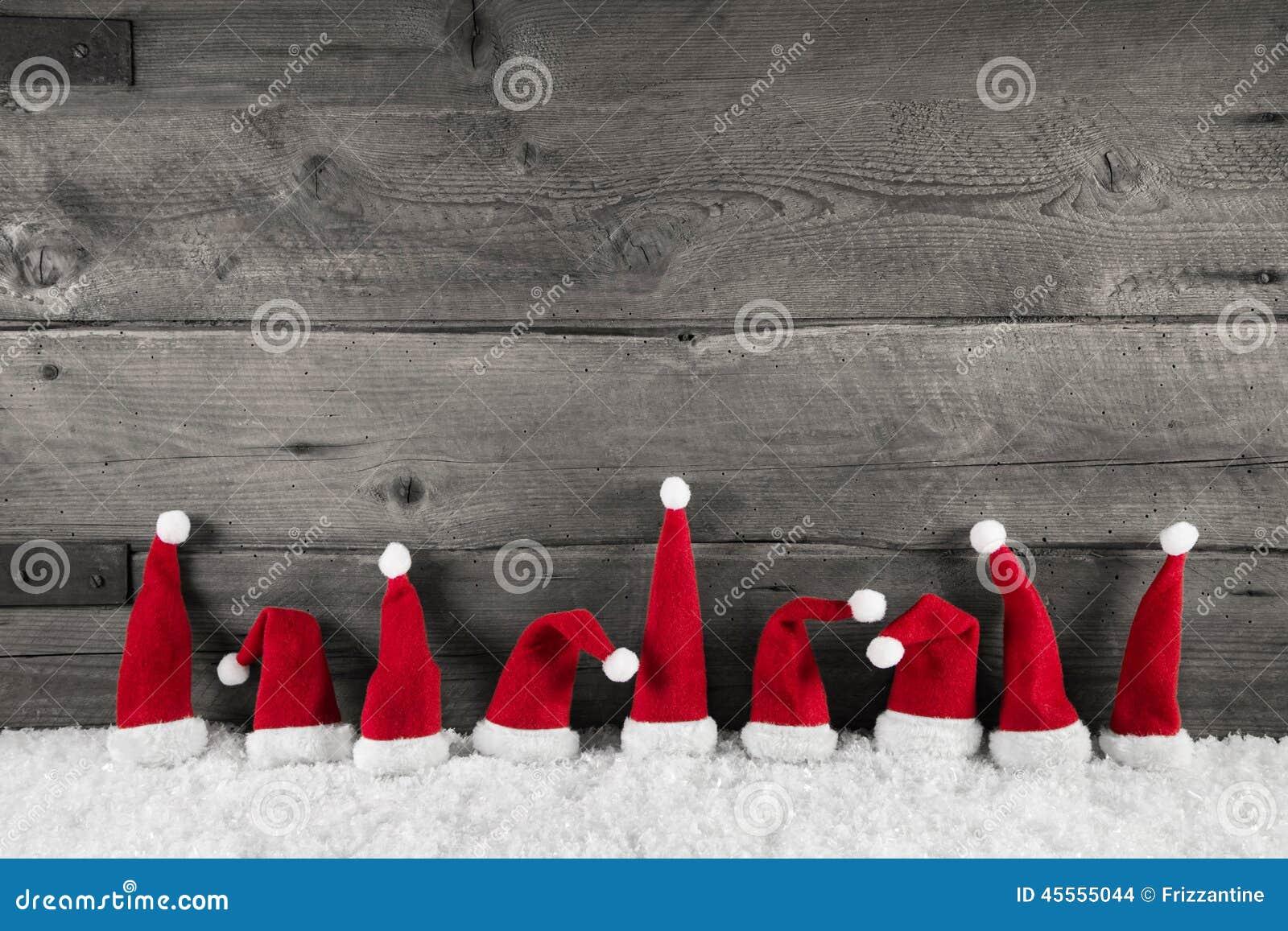 Fondo de madera de la Navidad con los sombreros rojos de santa para un franco festivo