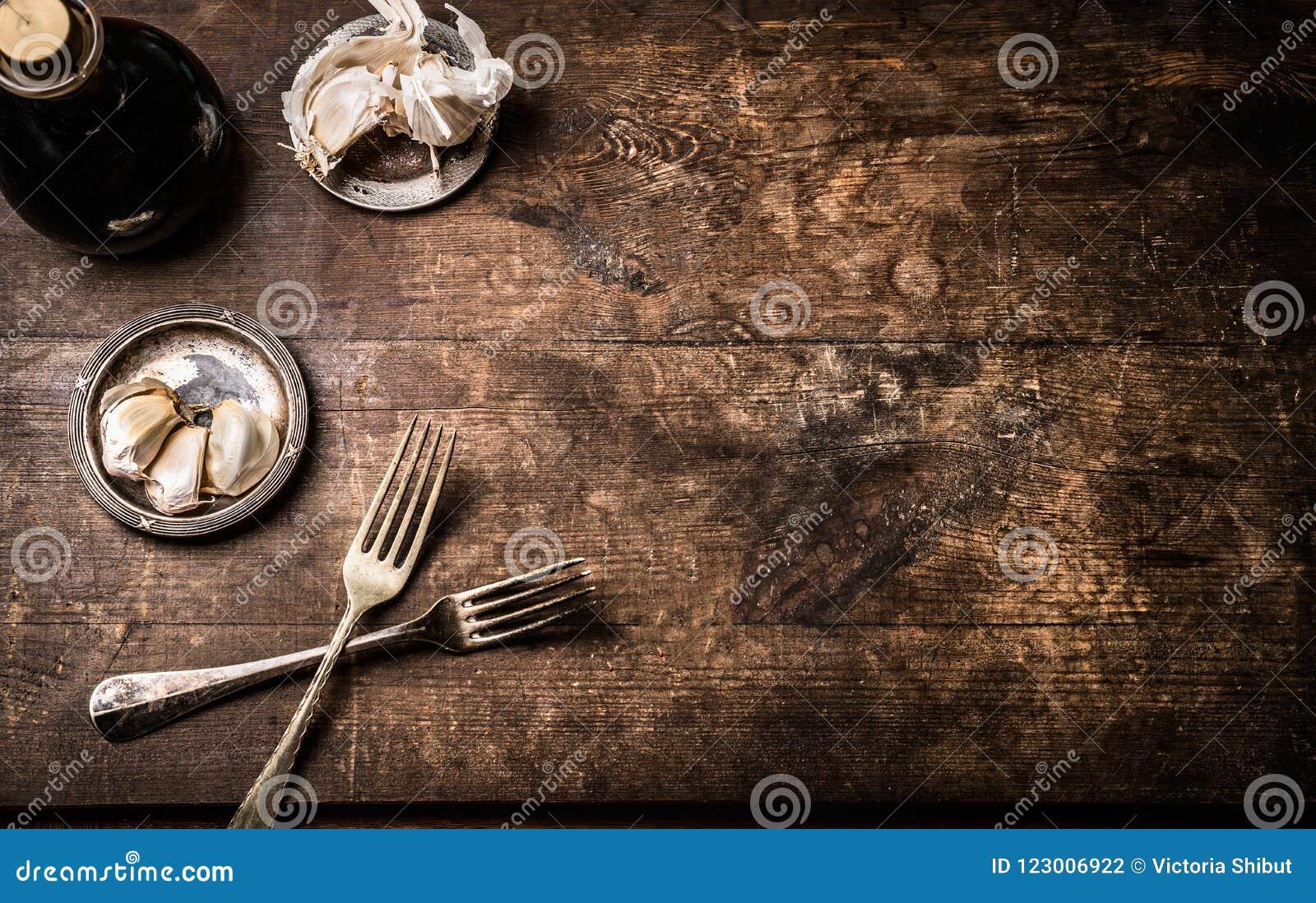 Fondo de madera envejecido rústico oscuro de la comida con los cubiertos y condimento, visión superior con el espacio para su dis