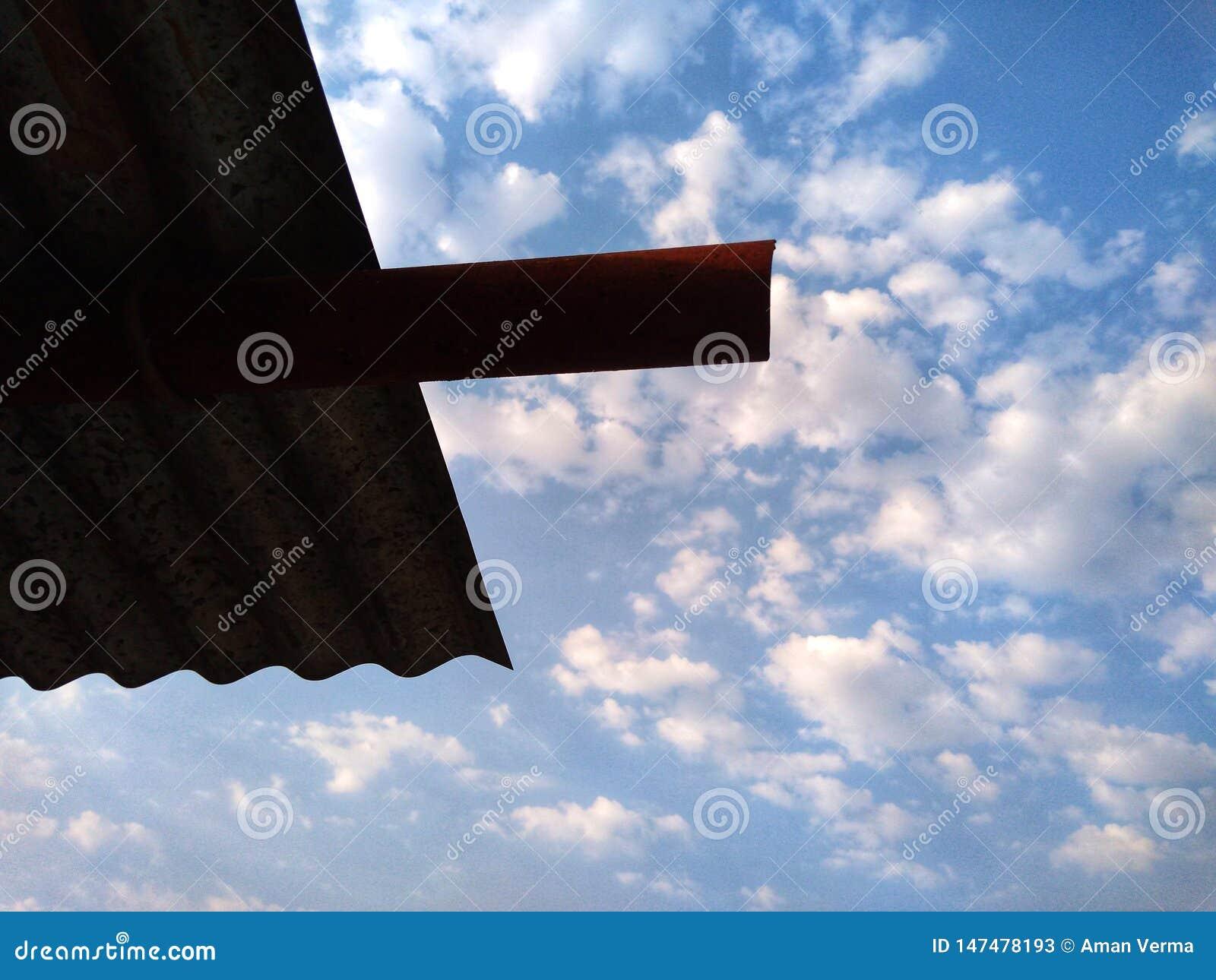 Fondo del cielo azul con las nubes y el tejado minúsculos