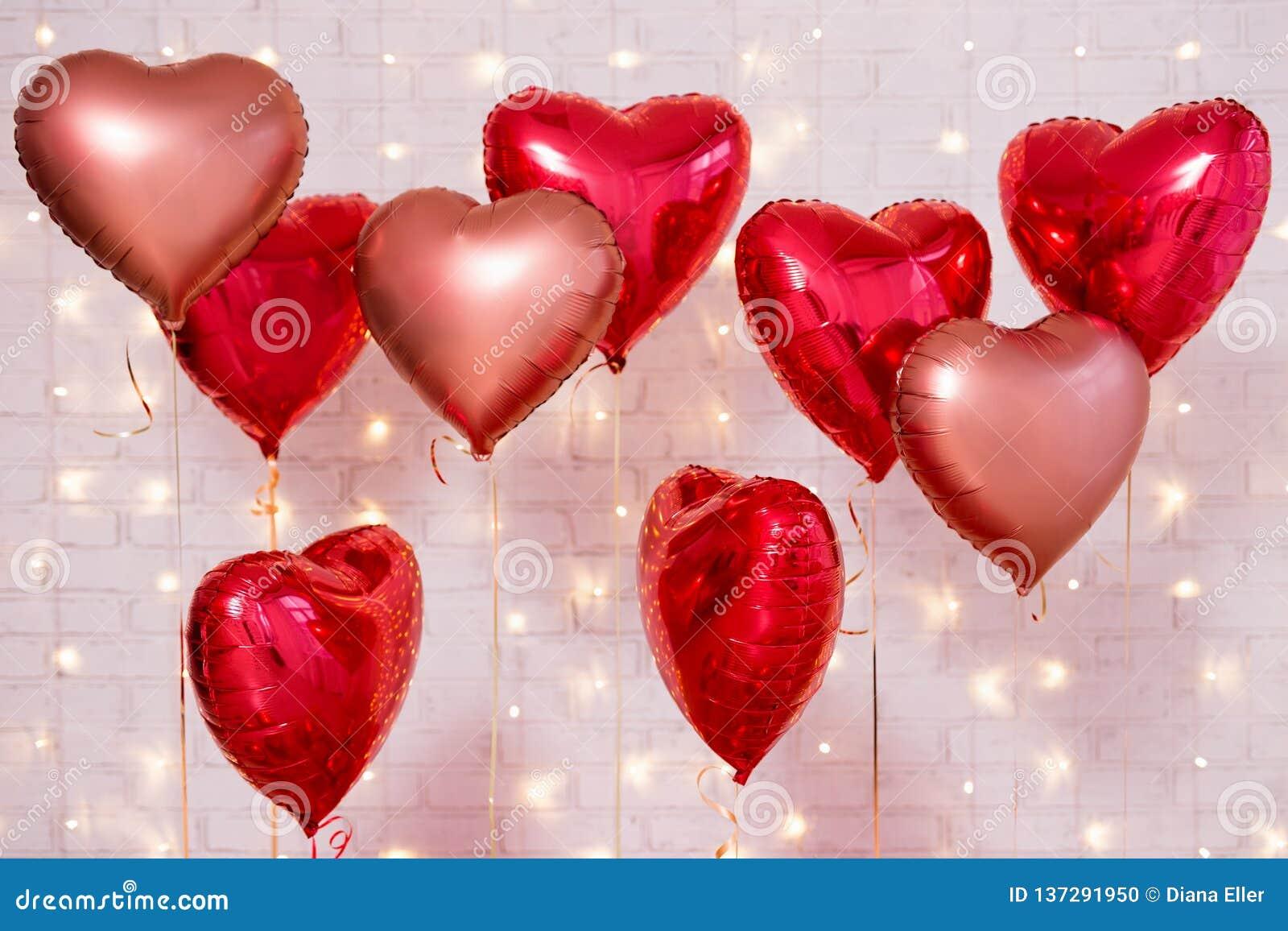 Fondo del día de tarjeta del día de San Valentín - grupo de globos en forma de corazón rojos sobre la pared de ladrillo