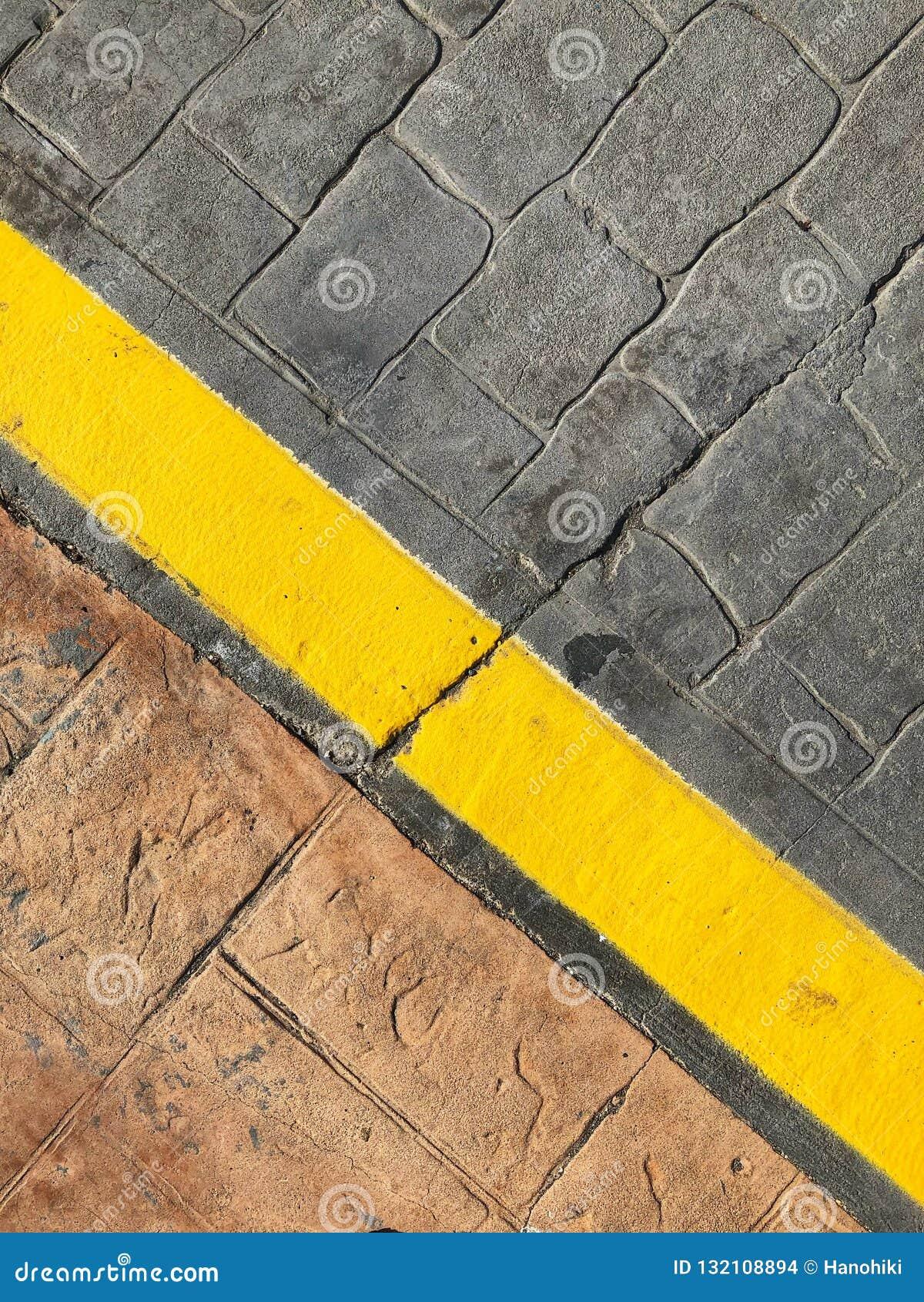Fondo del marciapiede - linea gialla sul confine della via della strada