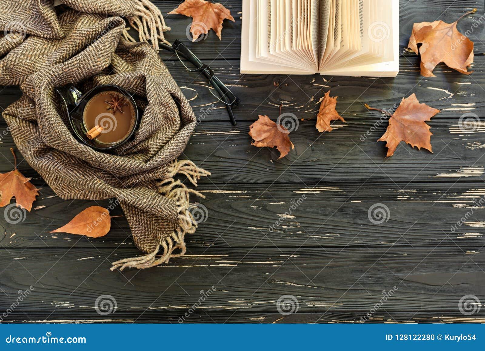 Fondo del otoño Taza de café, bufanda de la lana de cordero, lentes, libro abierto, hojas de arce en el fondo de madera negro, to