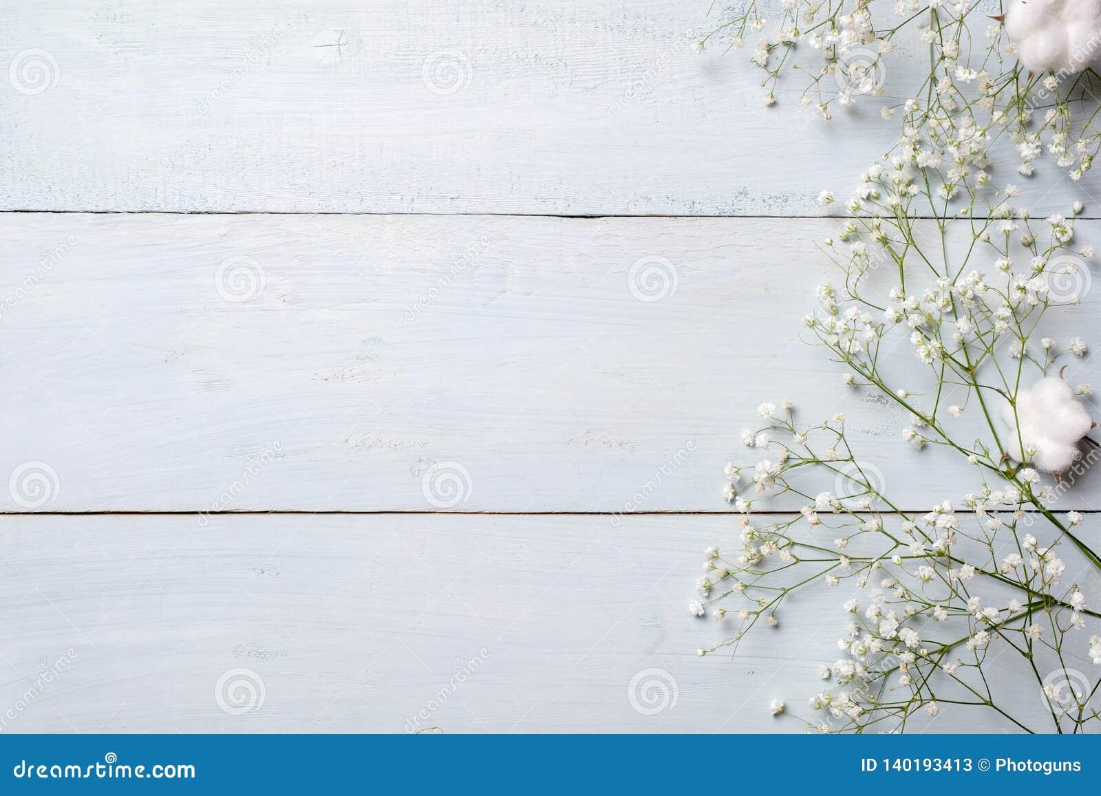 Fondo del resorte Flores rústicas blancas en la tabla de madera azul Maqueta de la bandera para la mujer o el día de la madre, pa