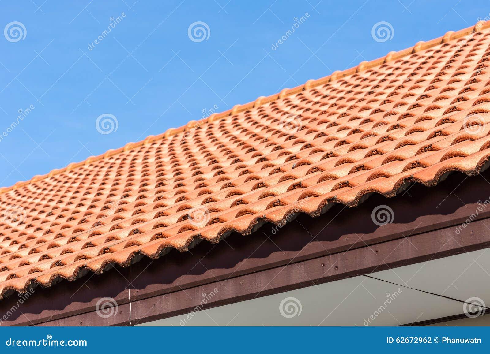 Fondo del tejado de tejas rojas y del cielo azul