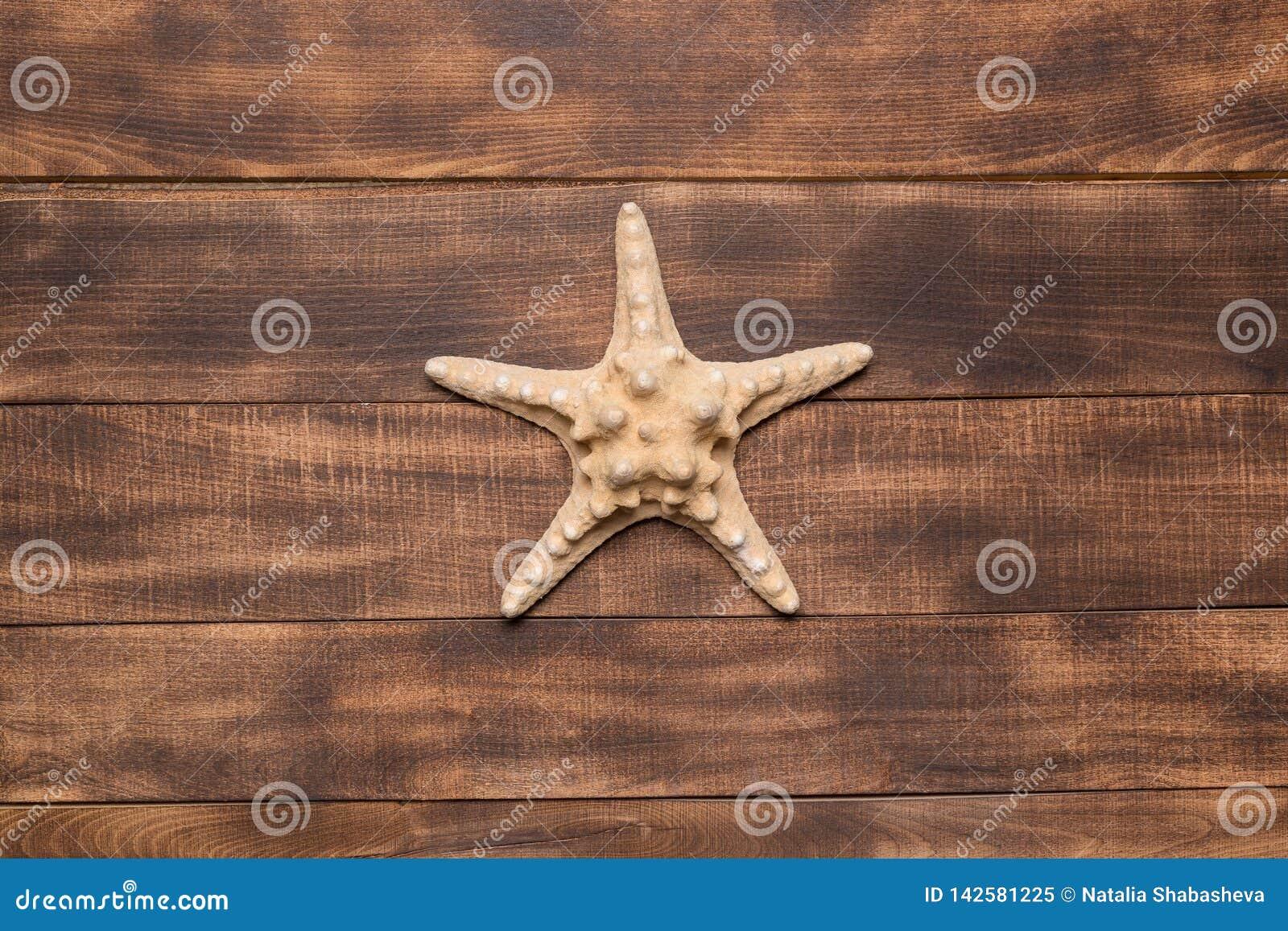 Fondo di estate, stella marina sui bordi di legno
