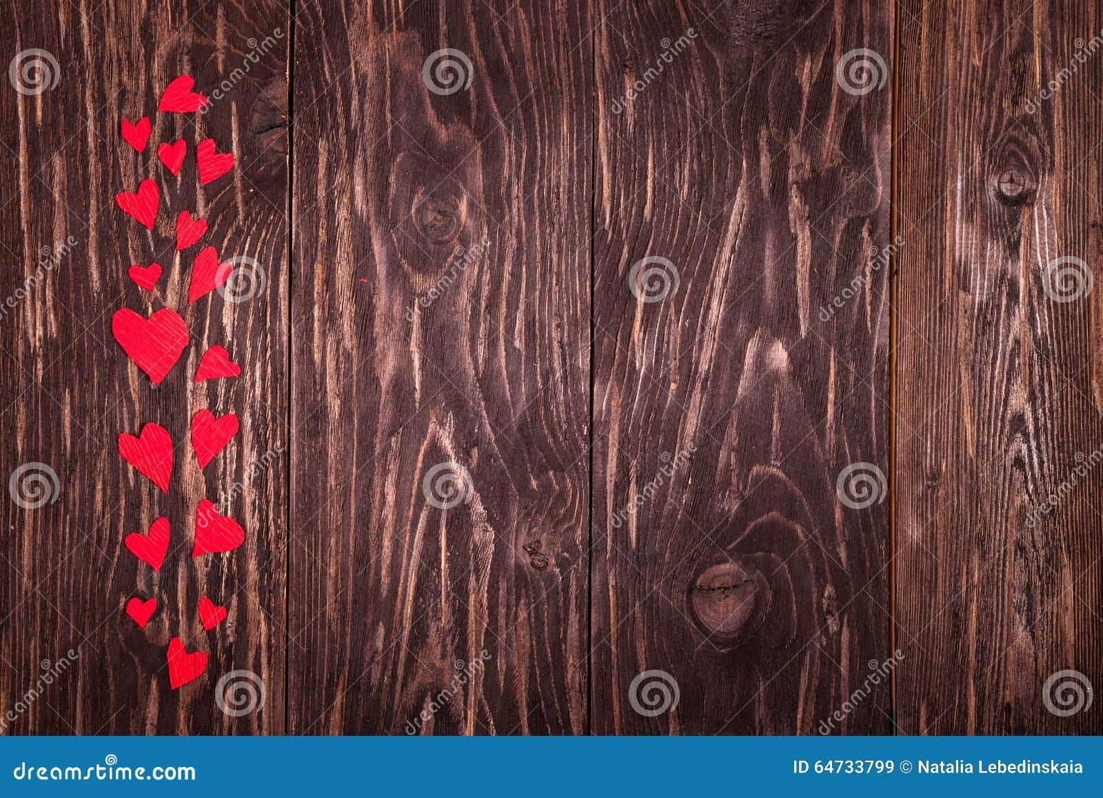 Fondo di legno dei piccoli cuori rossi