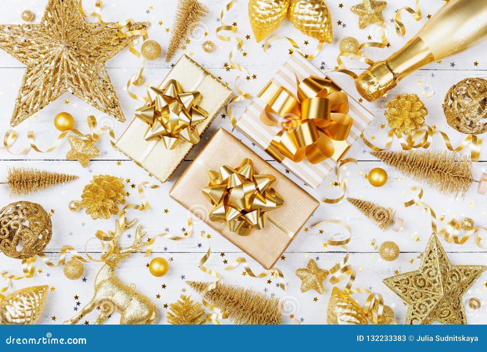 Fondo di Natale con il regalo dorato o scatola, champagne e decorazioni attuali di festa sulla vista bianca del piano d appoggio