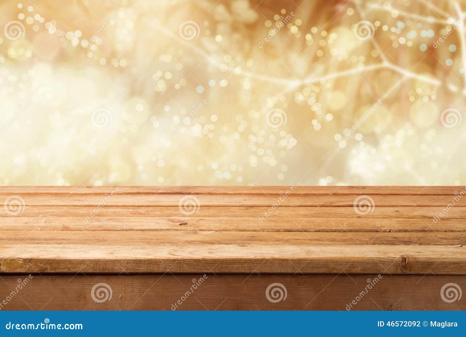 Fondo dorato del bokeh con la tavola di legno vuota per l esposizione del montaggio del prodotto