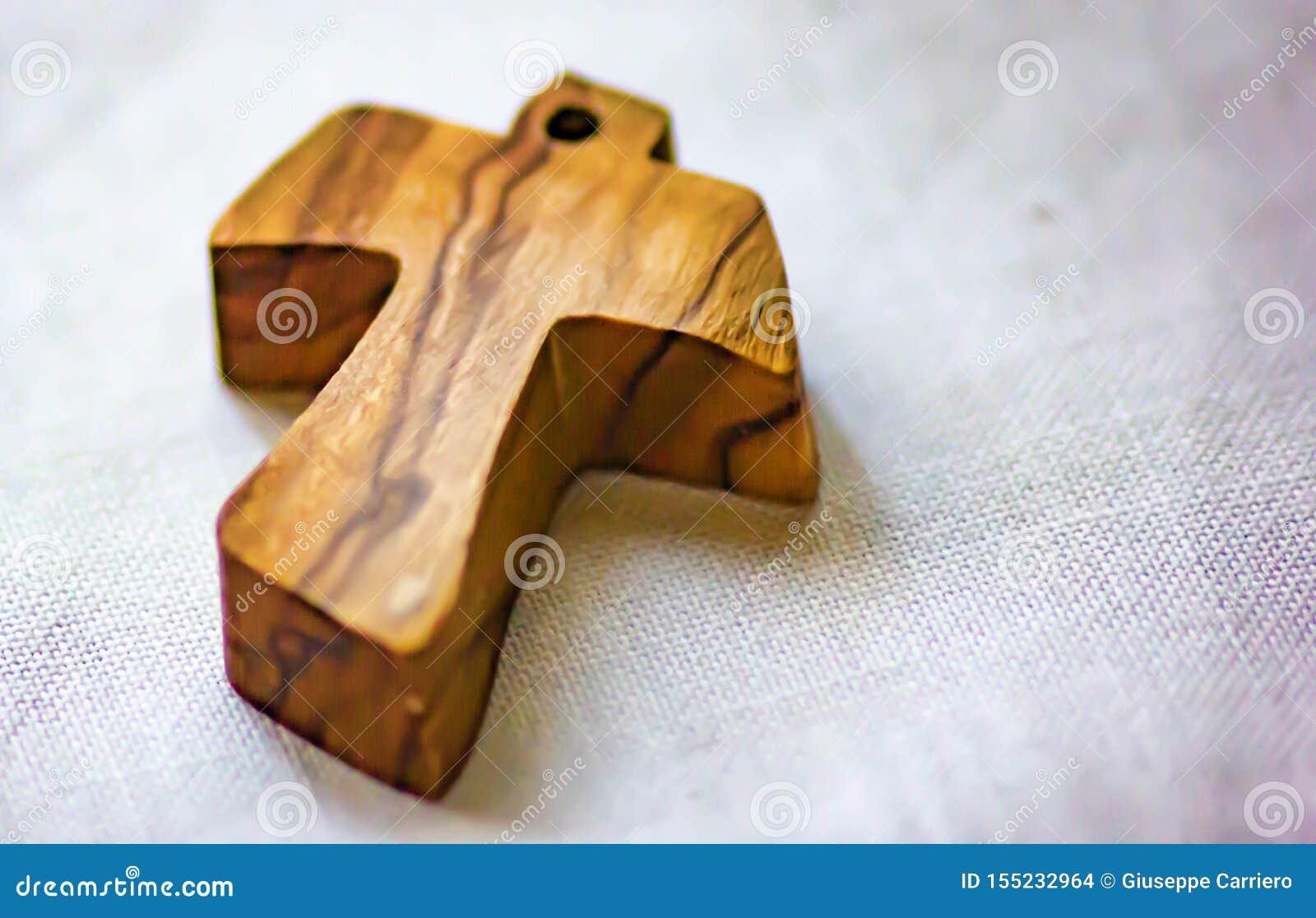 Fondo, imagen de una pequeña cruz de madera puesta en la tela de lino usada como colgante por algún fiel