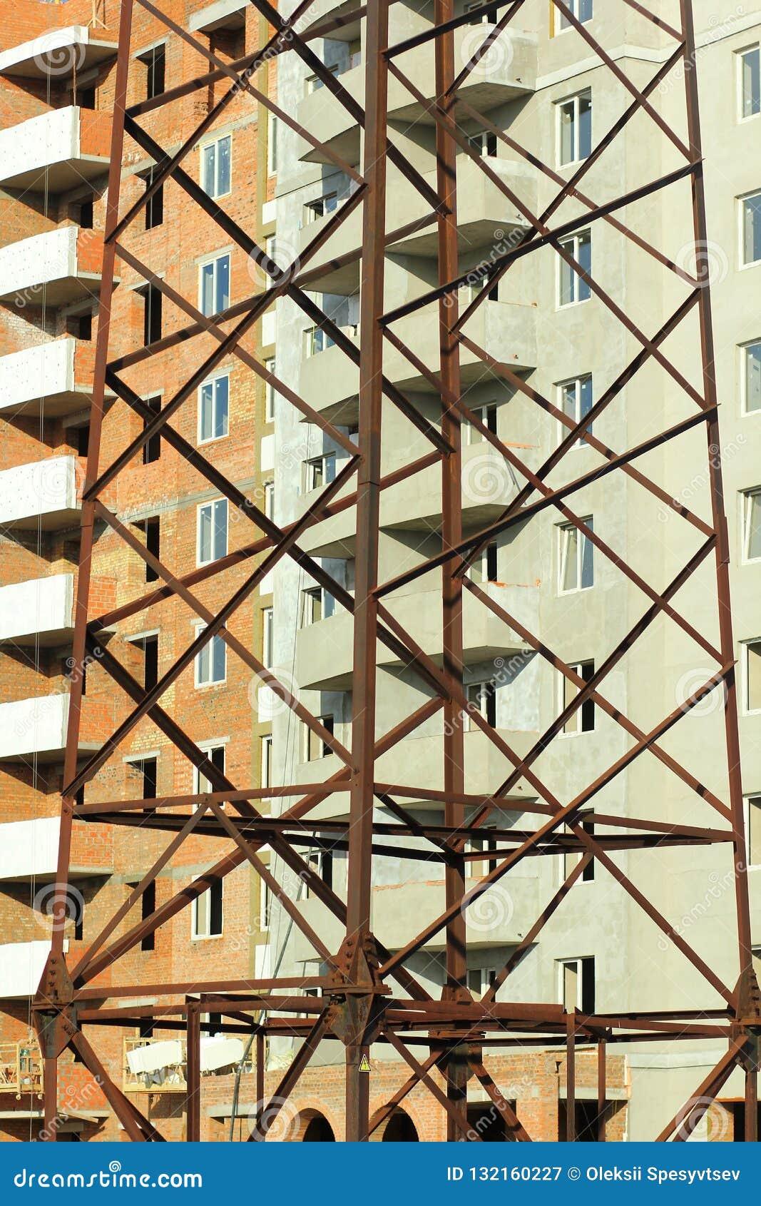 Fondo industriale verticale dell estratto della costruzione a più piani del mattone in costruzione dietro la fine sulle linee ele