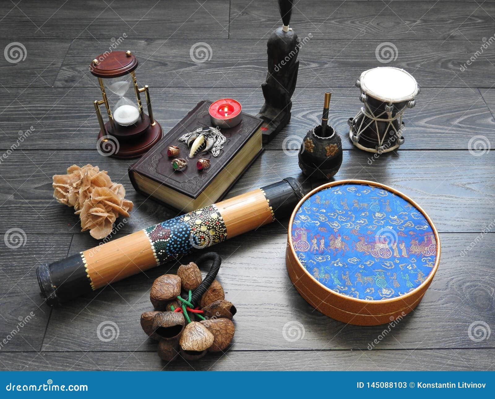 Fondo mistico con un vecchio libro, le candele ed altri attributi Halloween ed il concetto occulto del rituale di magia nera