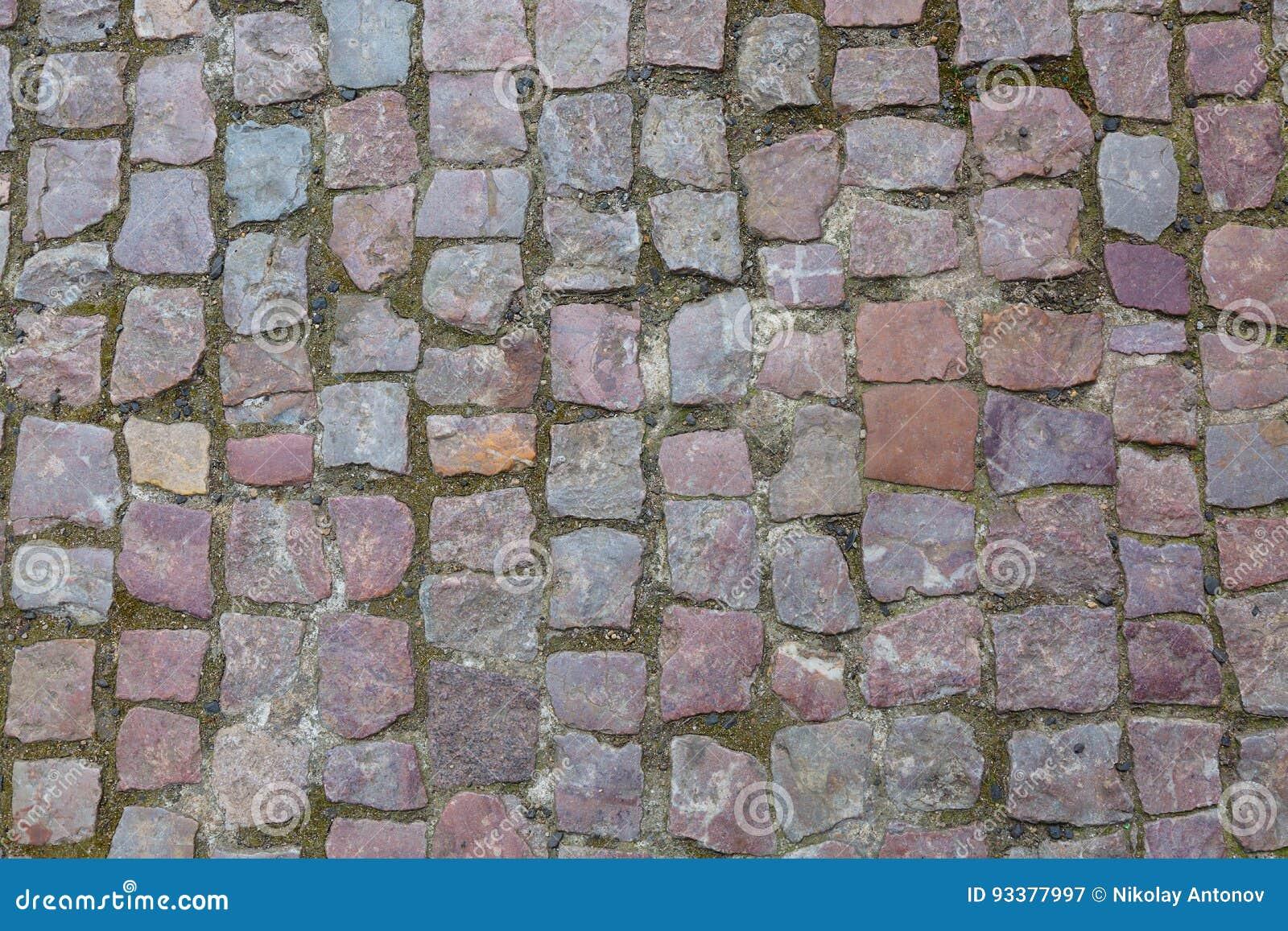 Fondo o struttura cobblestoned della pavimentazione del granito di pietra Fondo astratto di vecchio primo piano della pavimentazi