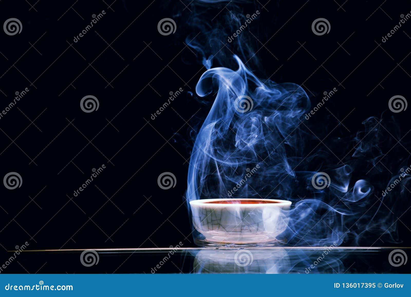 Fondo oscuro de té negro del humo chino de la taza nadie