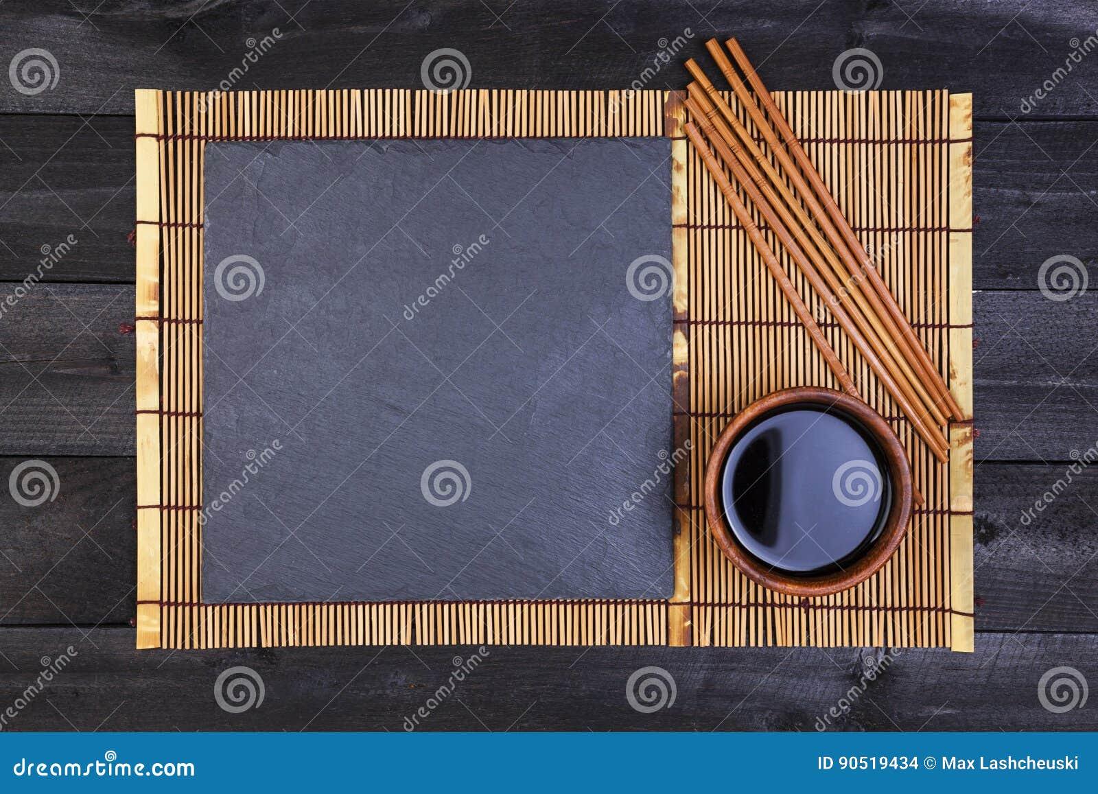 Fondo per i sushi Salsa di bambù di soia e della stuoia sulla tavola di legno nera Vista superiore con lo spazio della copia