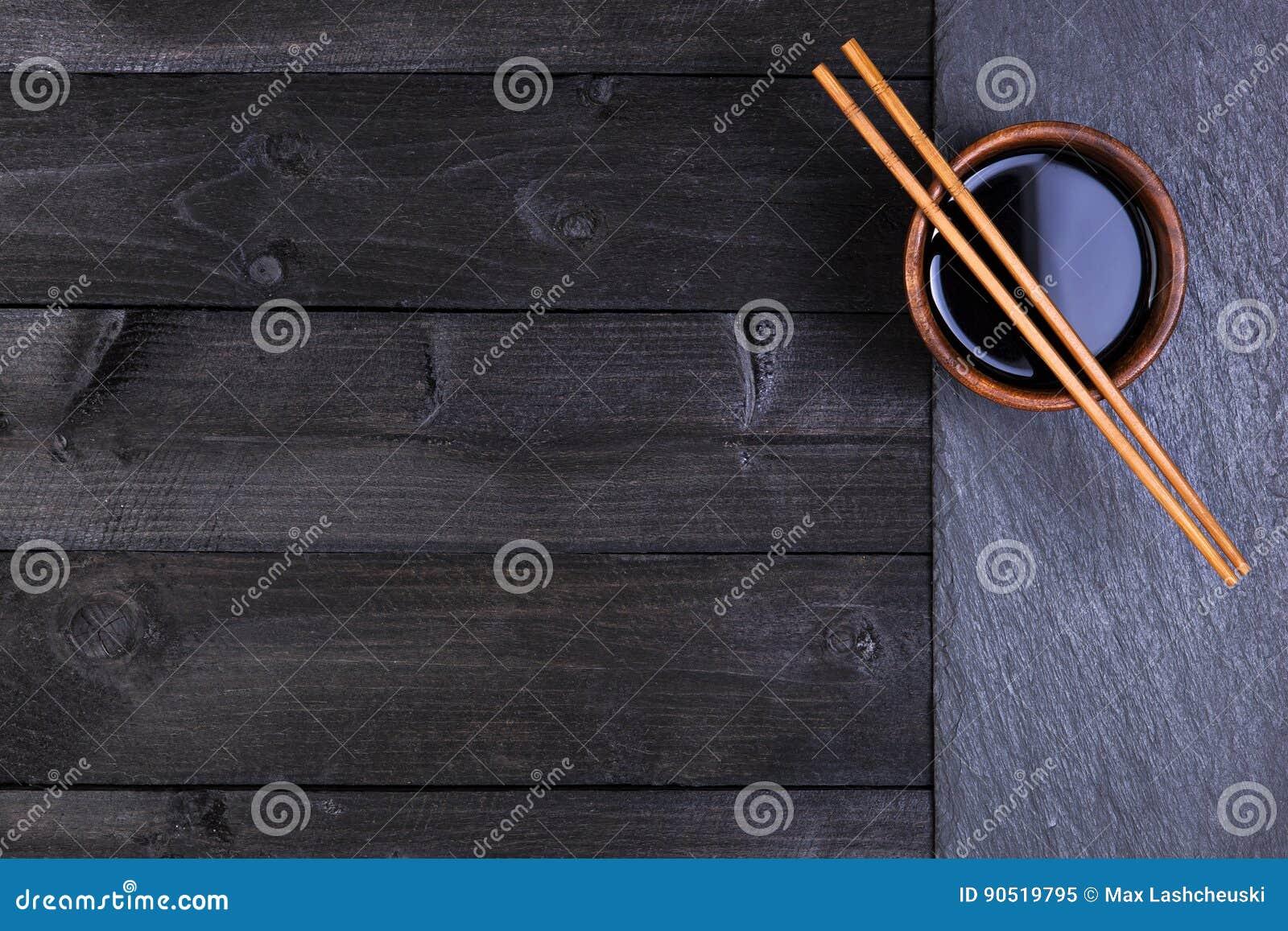 Fondo per i sushi Salsa di soia, bastoncini sulla pietra nera Vista superiore con lo spazio della copia