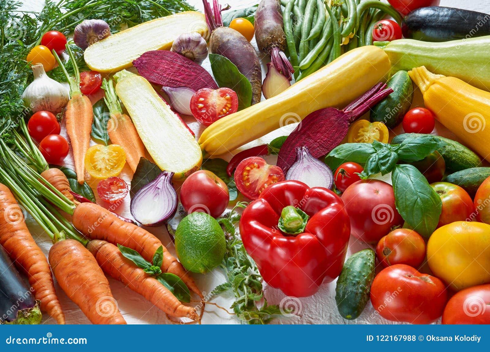 Fondo vegetariano sano de la comida de la dieta Diversas verduras orgánicas frescas en la tabla blanca: tomates, calabacín cortad