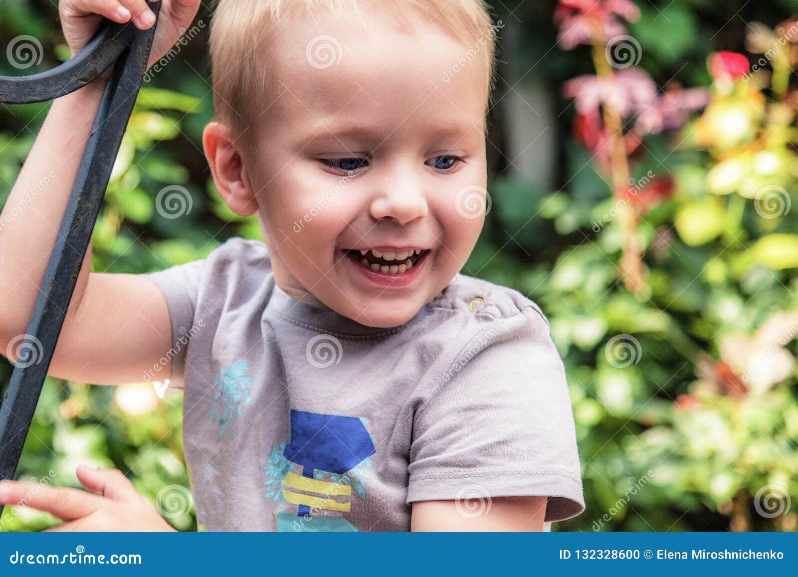 Fondo verde sonriente de las flores del ot al aire libre del bebé lindo