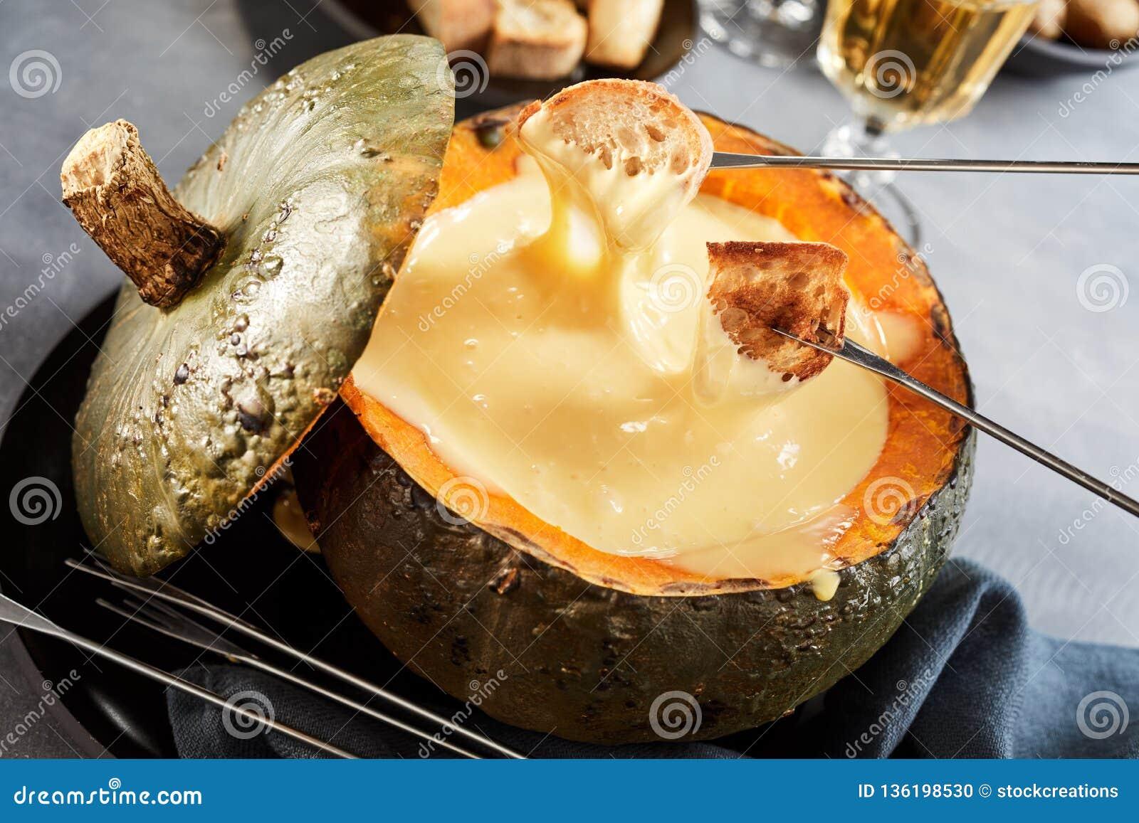 fondue  de queso cremosa en una calabaza o una calabaza