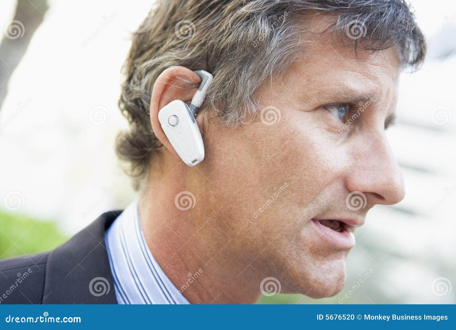 Fone de ouvido desgastando do homem de negócios ao ar livre