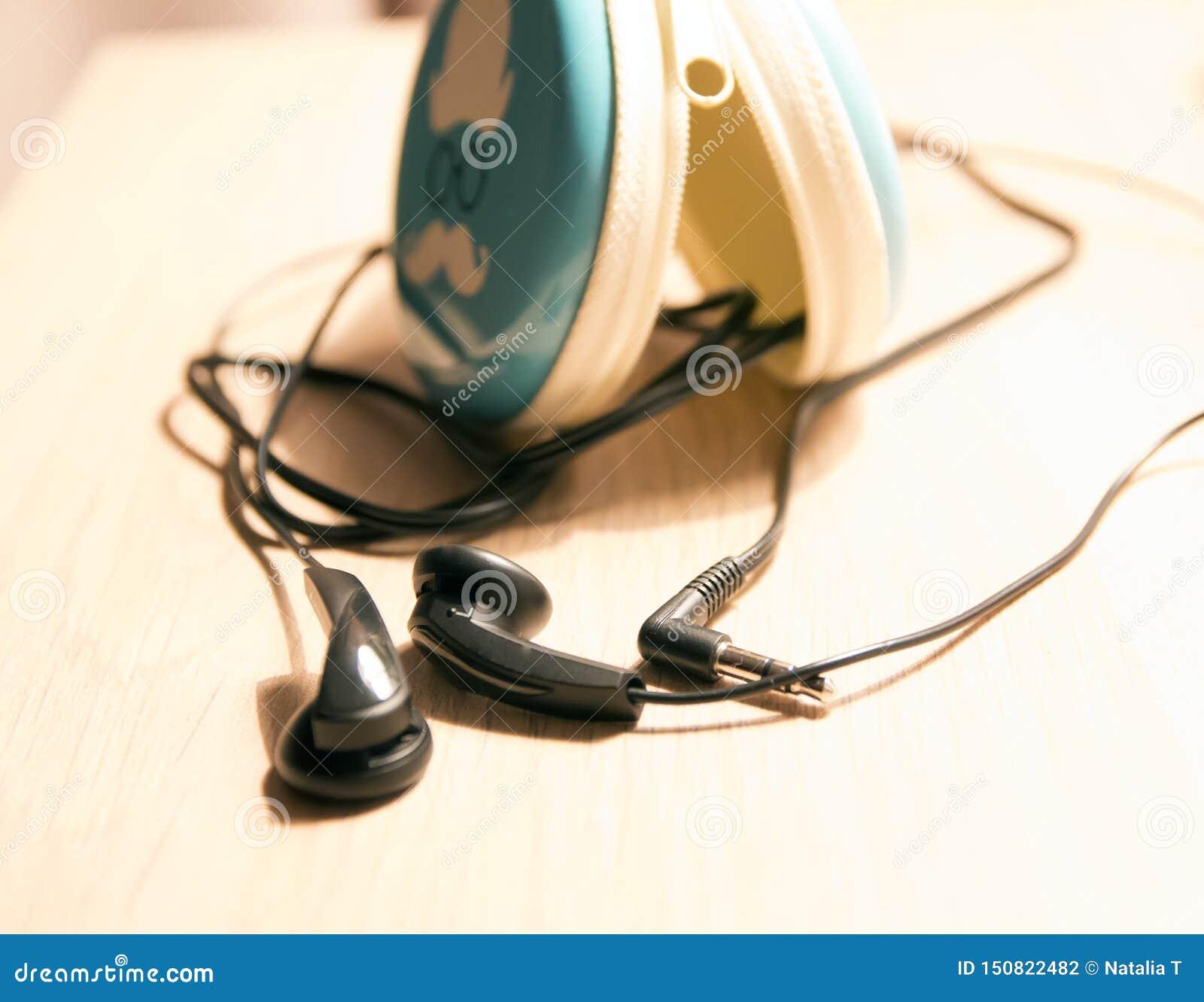 Fones de ouvido com fios na tabela, com, uma caixa para fones de ouvido