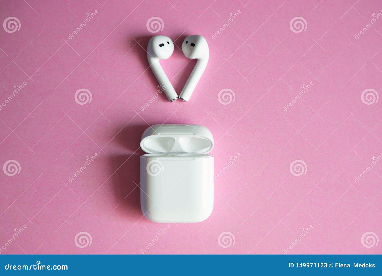 Fones de ouvido sem fio brancos que encontram-se sobre um carregador aberto em um fundo cor-de-rosa Lugar para o texto
