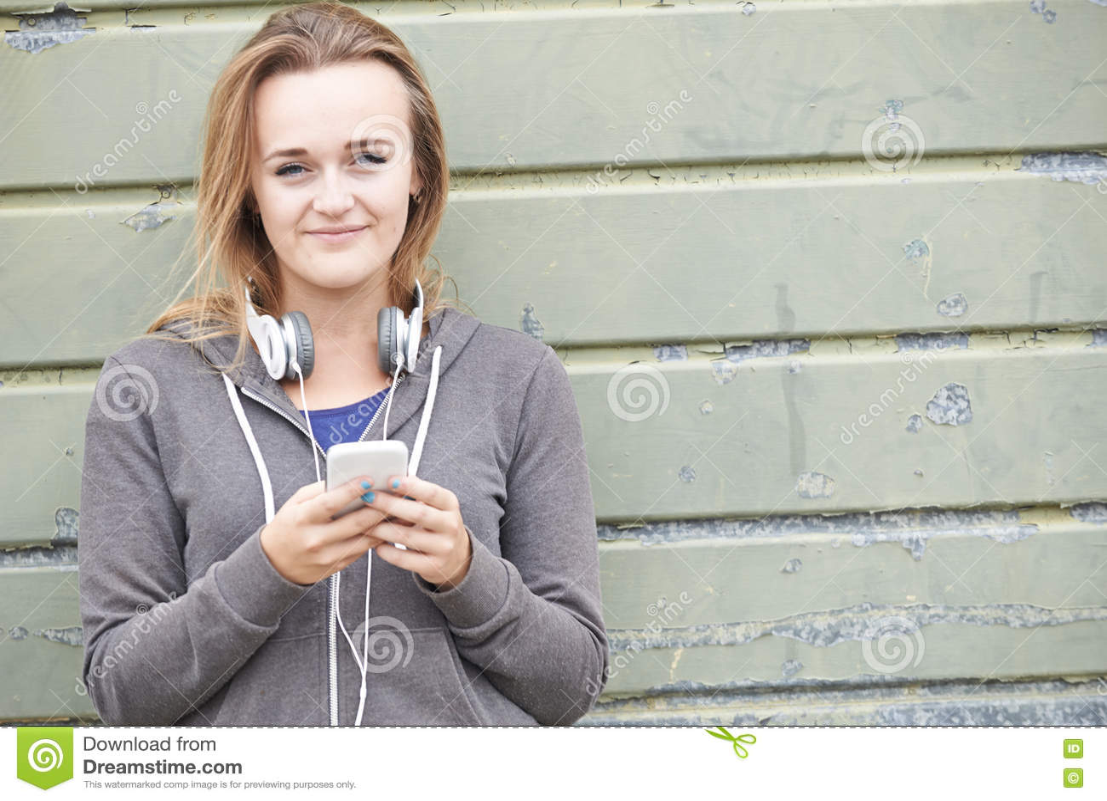 Fones de ouvido vestindo do adolescente e escuta a música em urbano