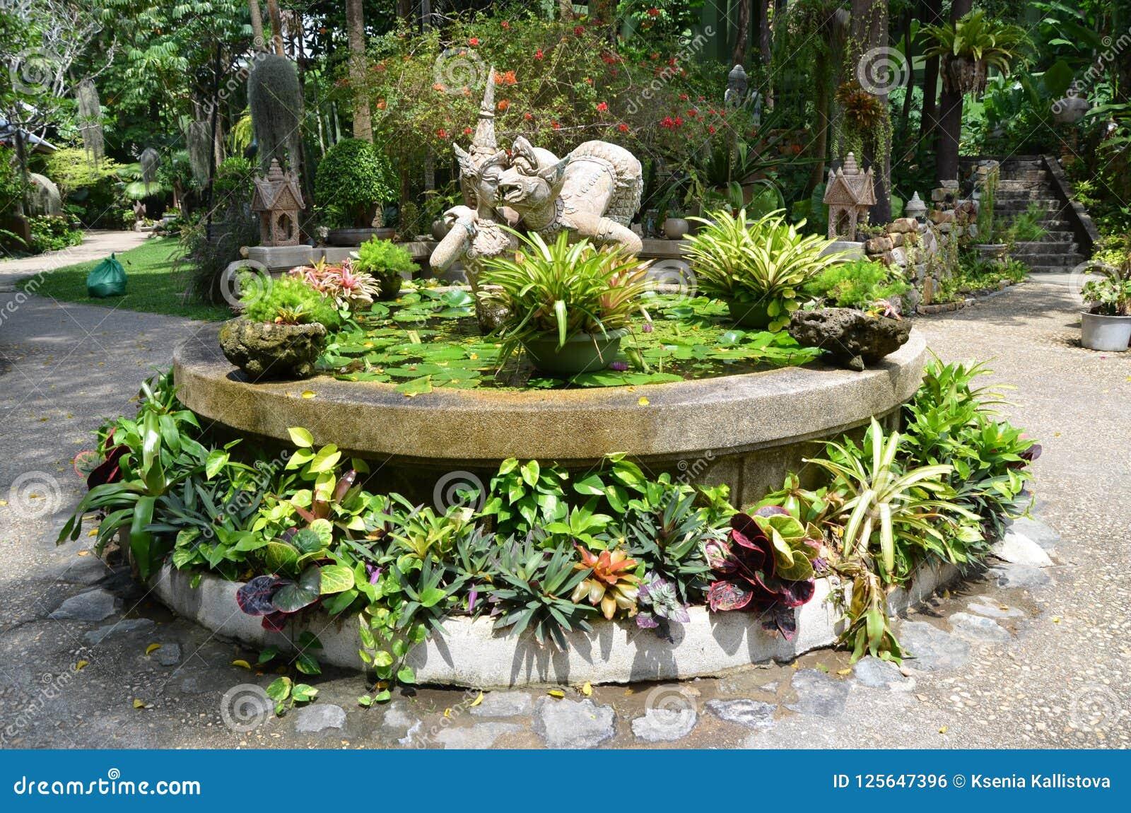 Fontain med blommor och skulptur