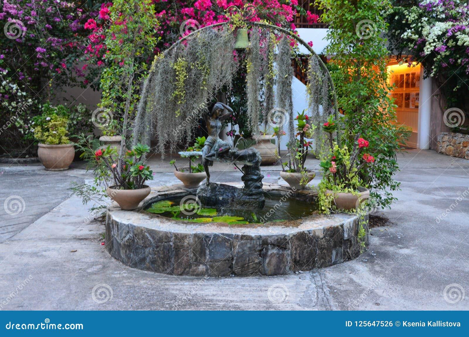 Fontain mit Blumen und Bäumen um es