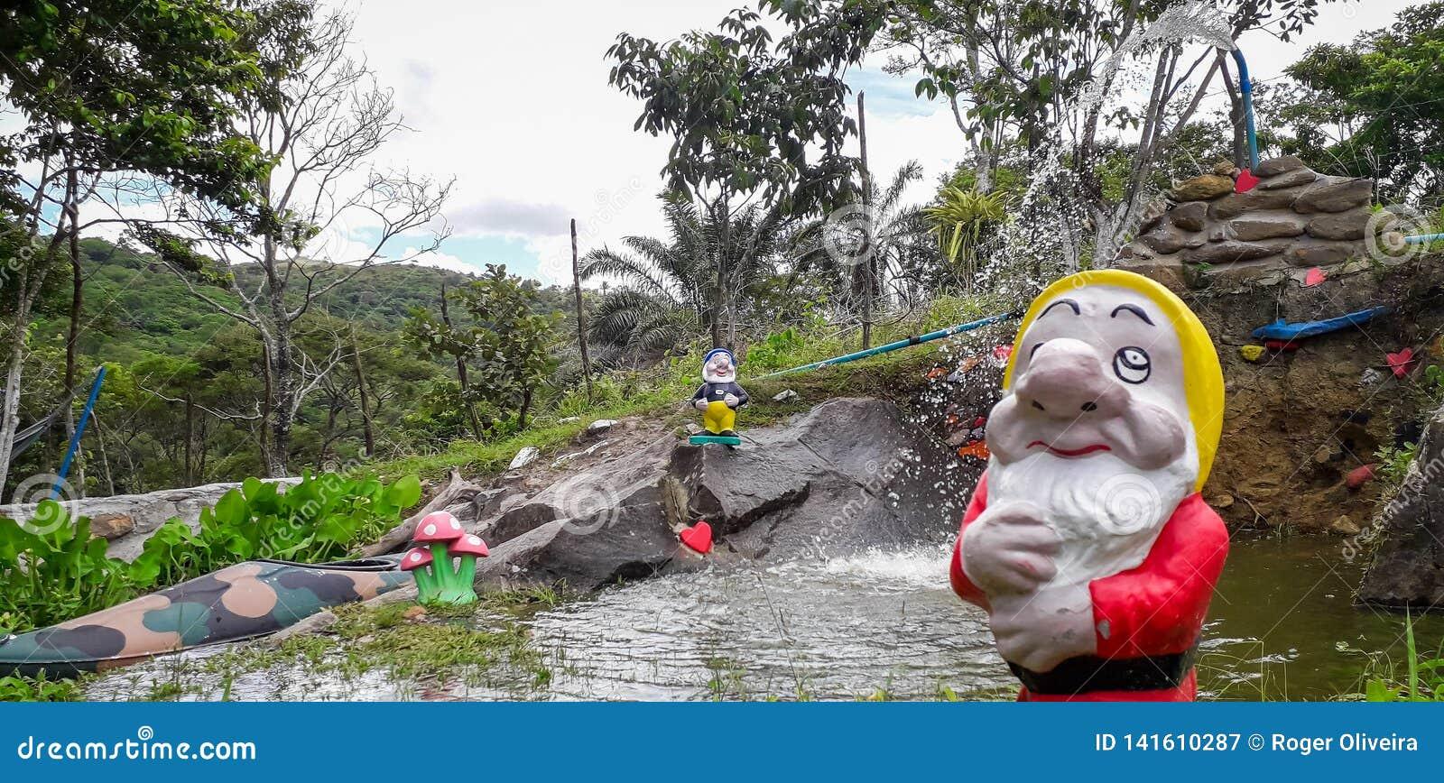 Fontaine d eau et un Gnome de jardin avec la boîte d arrosage devant arbres