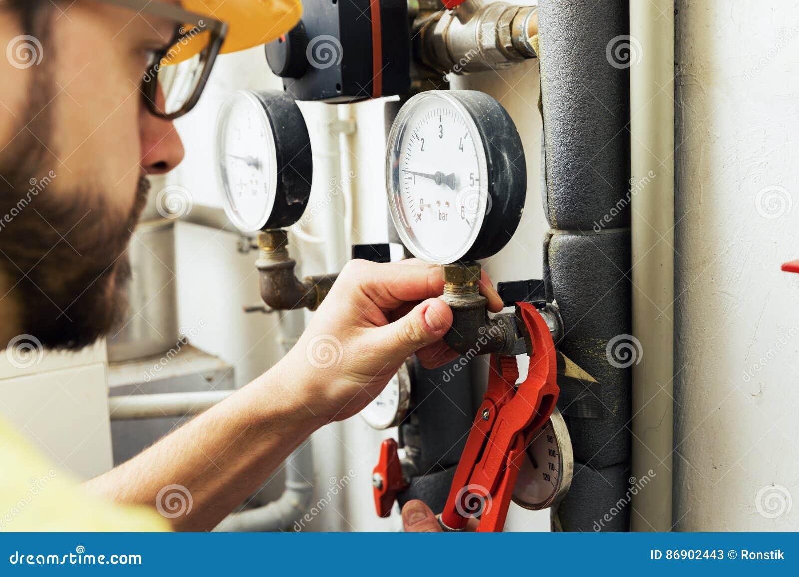 Fontanero que instala el metro de la presión para el sistema de calefacción