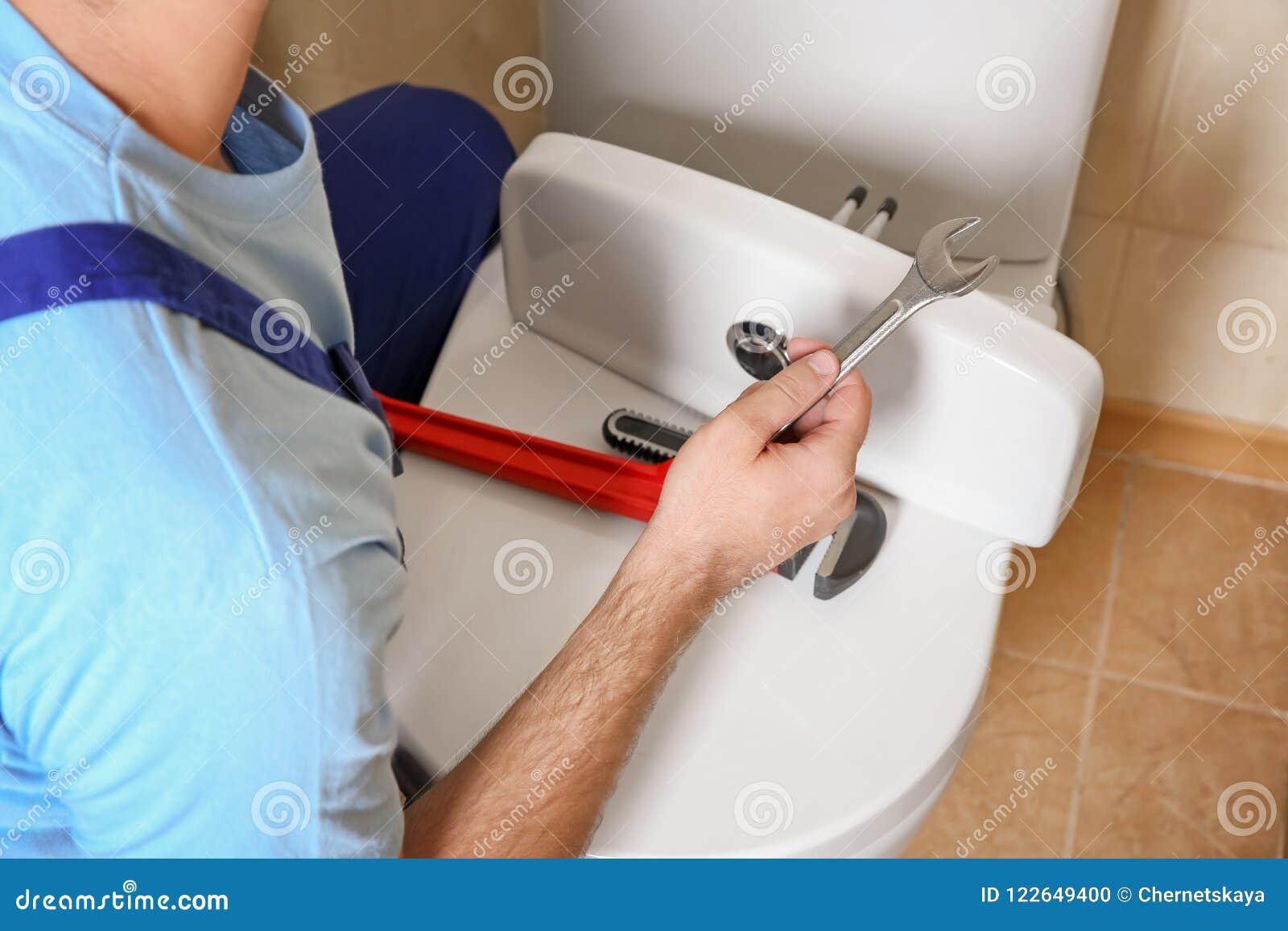Fontanero que repara el retrete con la llave dentro