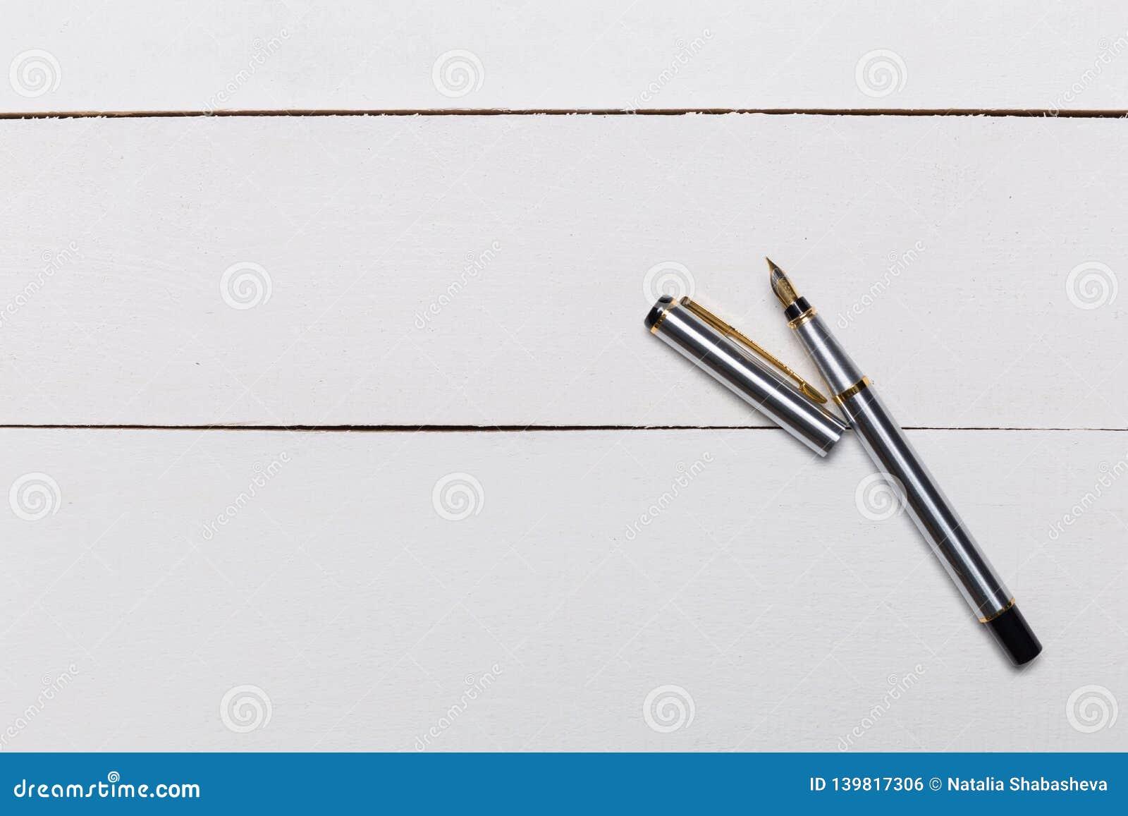 Fontanny pióro na białym drewnianym tle
