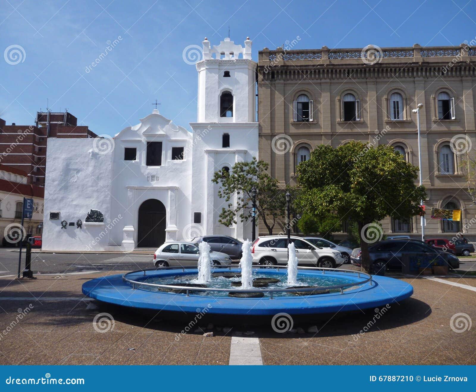 Fonte redonda azul na frente de uma igreja branca